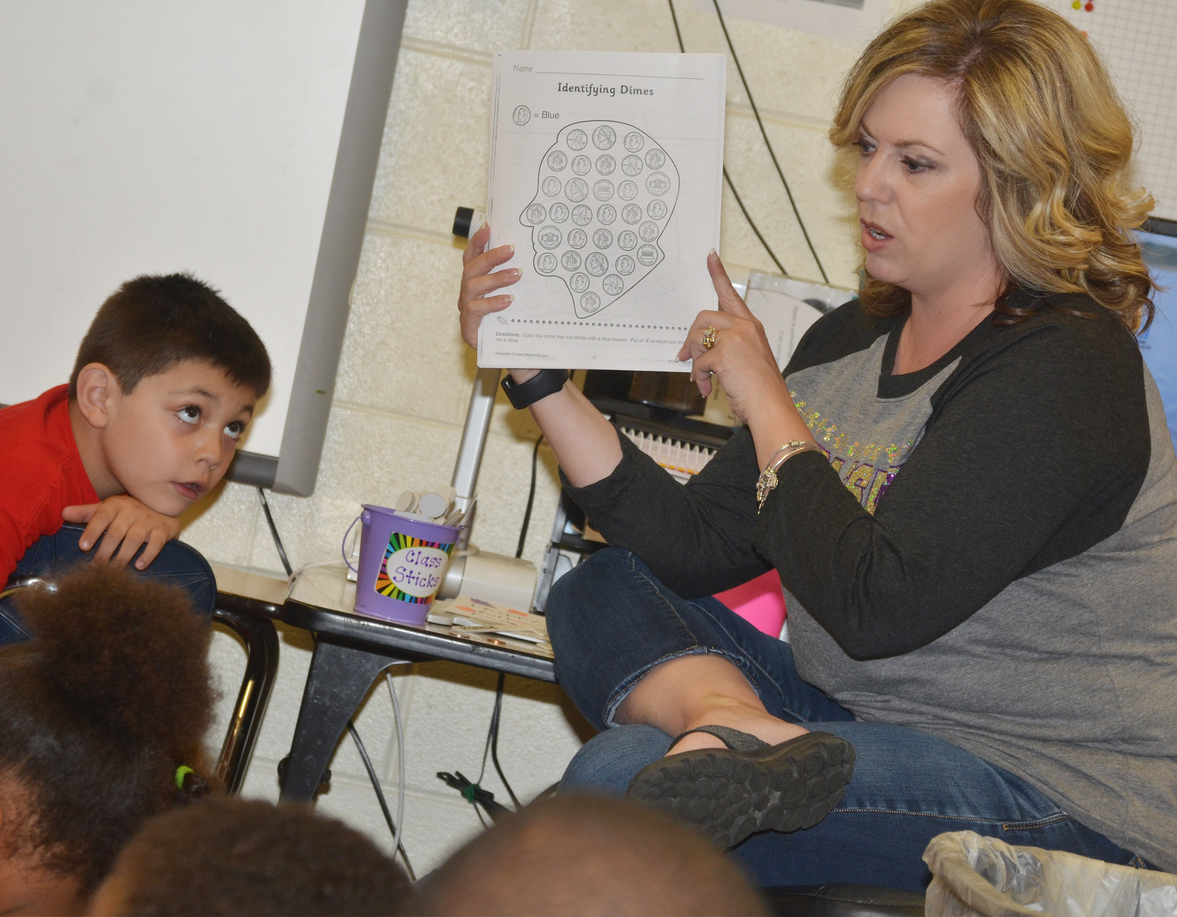 CES kindergarten teacher Nikki Price talks to her students about how they can identify dimes and nickels.