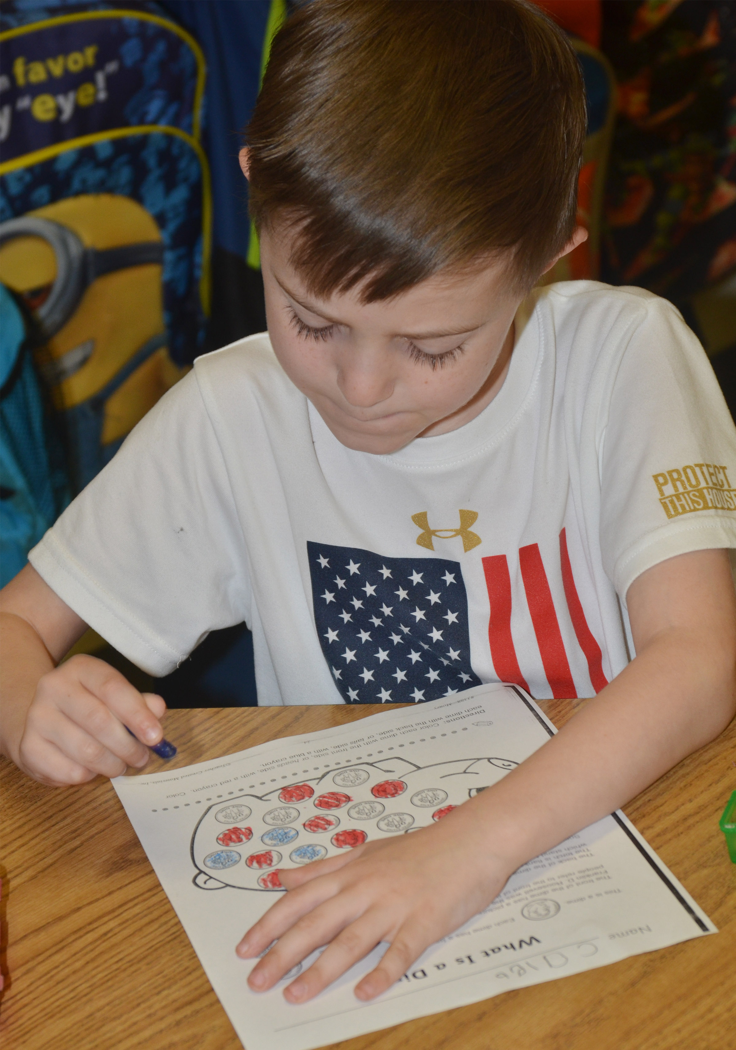 CES kindergartener Caleb Goodson colors dimes.