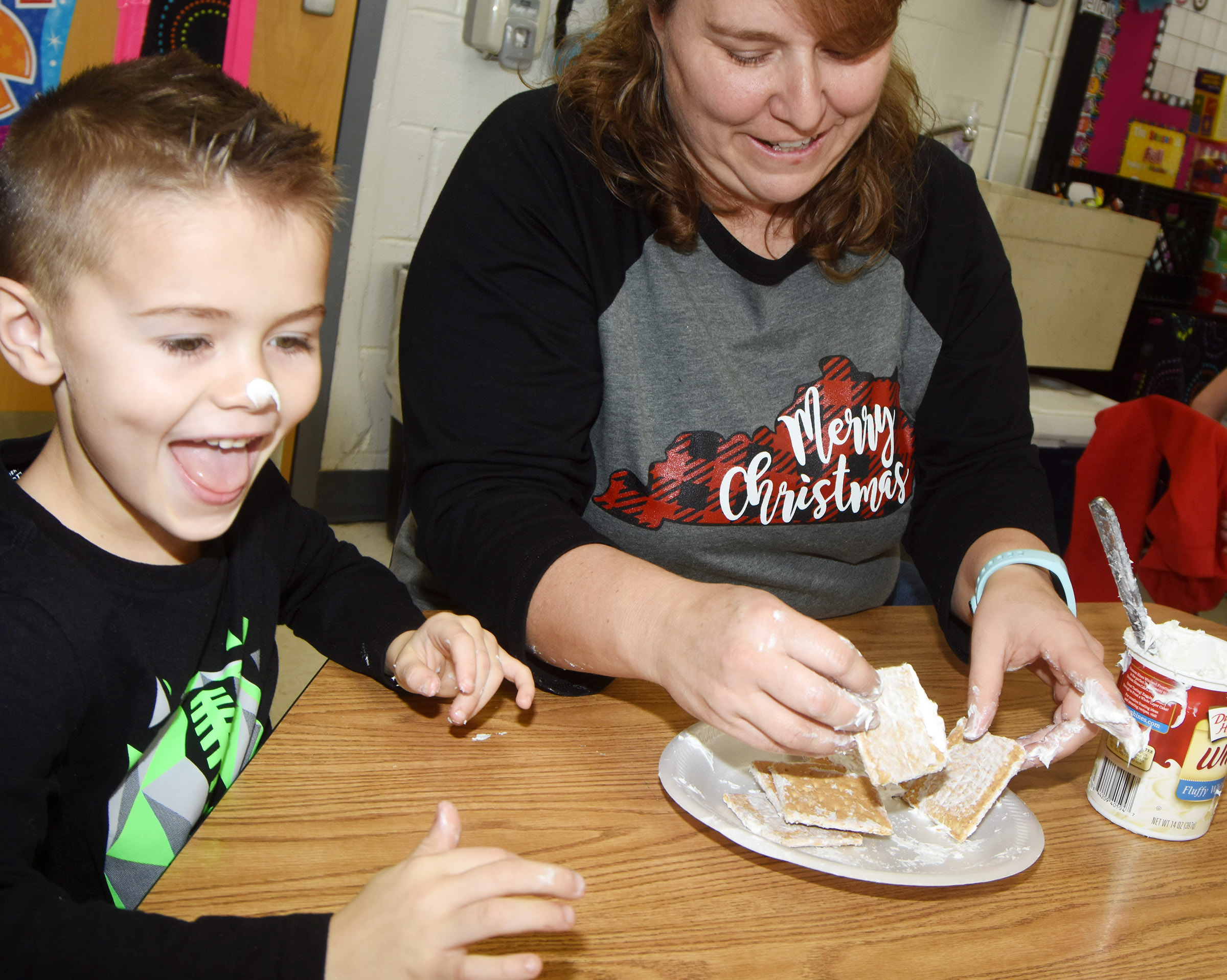 CES kindergarten assistant Wanda Swafford puts icing on Tate Jones's nose as they build a gingerbread house together.