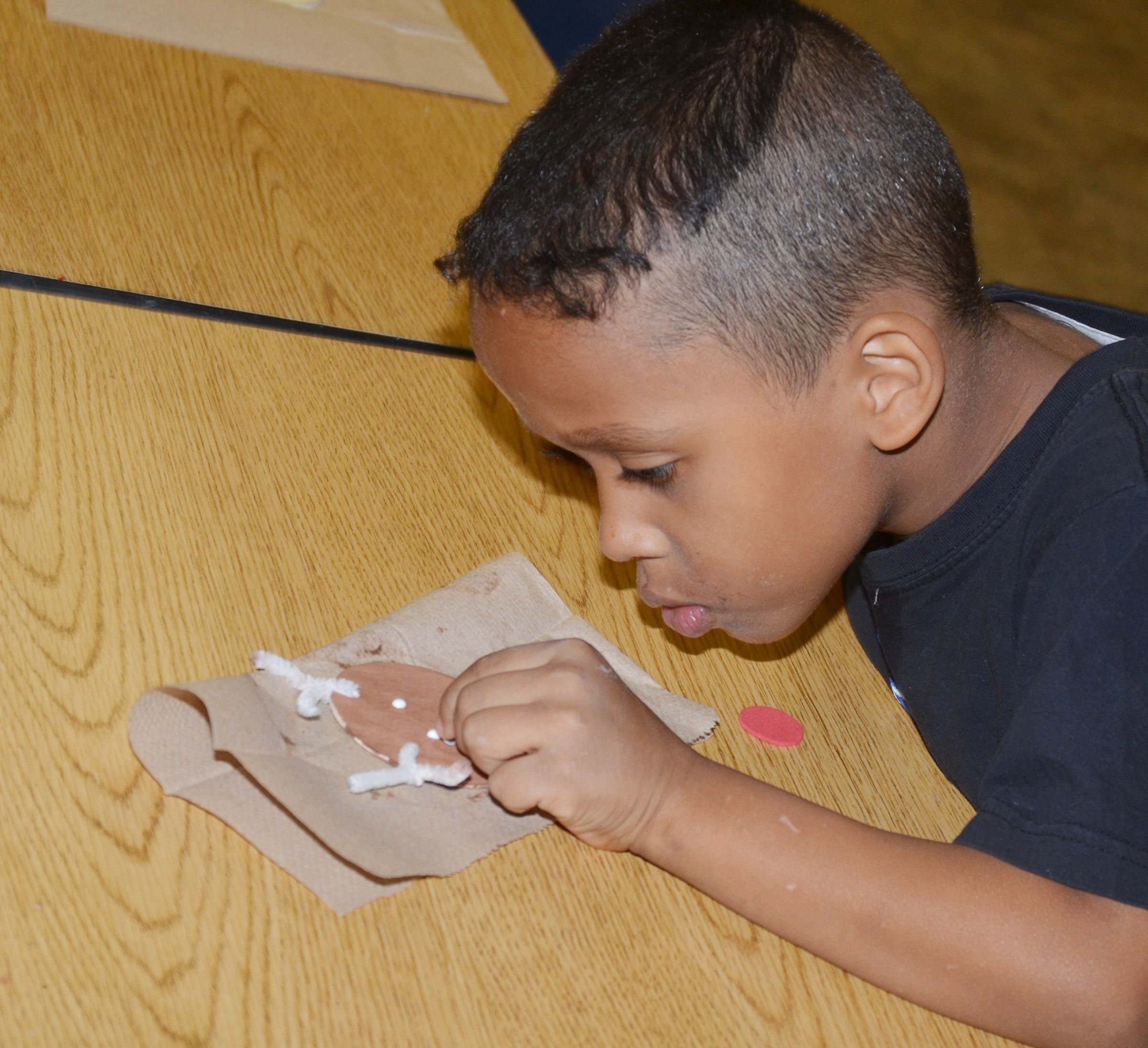 CES first-grader Gabriel Jolivert carefully adds eyes to his reindeer ornament.