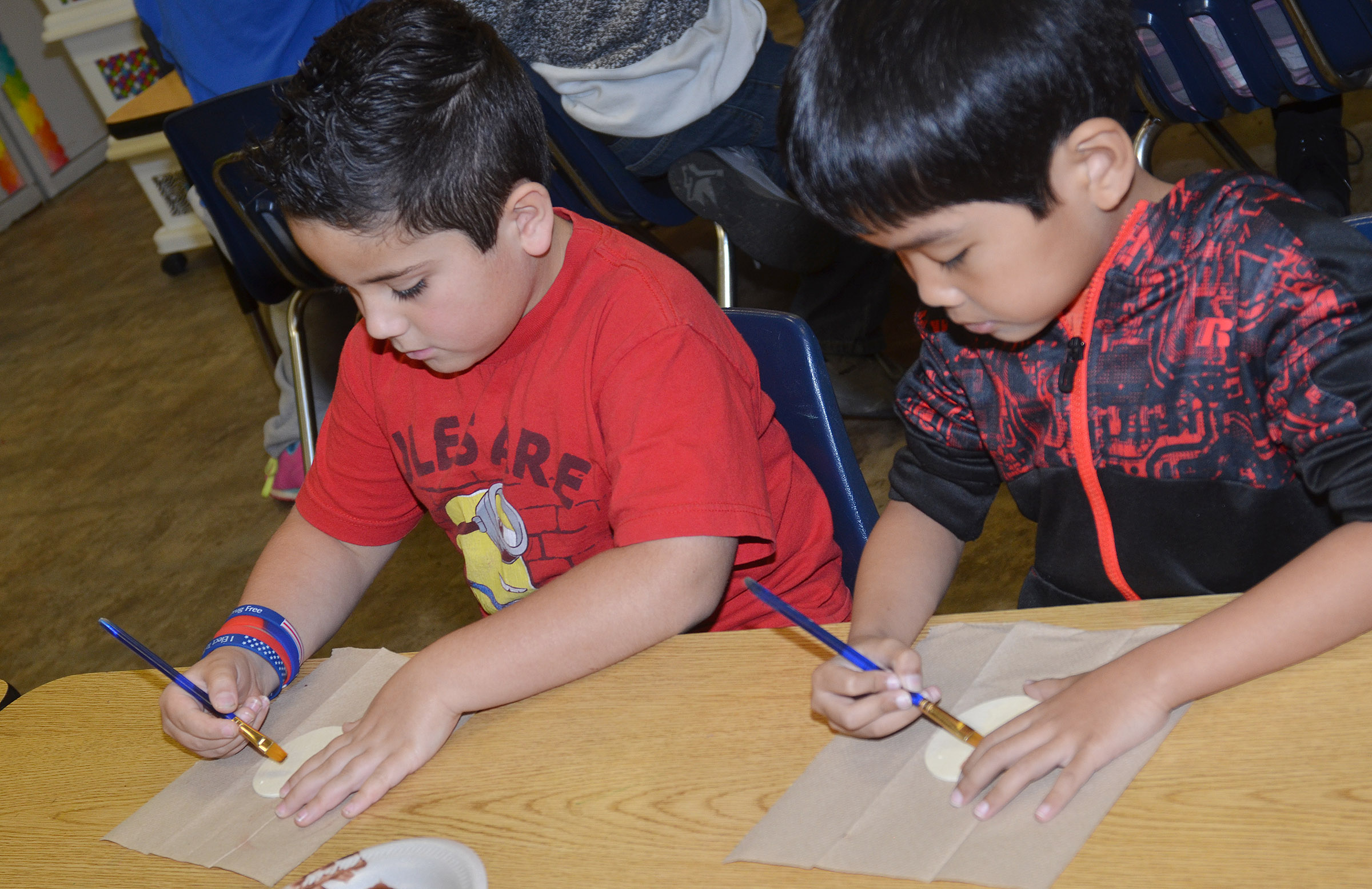 CES second-graders Nicholas Almeida, at left, and Zach Hak paint their reindeer ornaments.