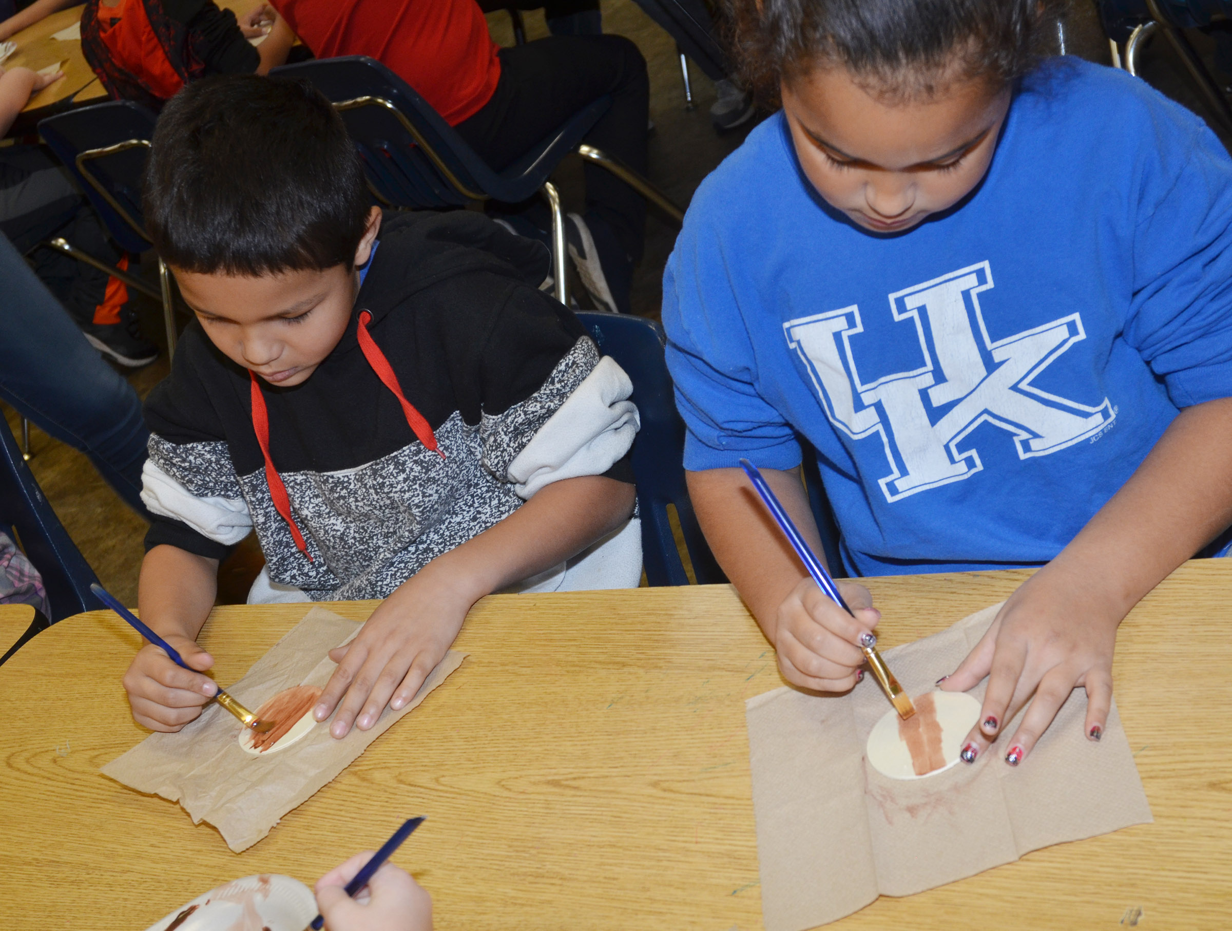 CES second-graders Makyian Bridgewater, at left, and Maleigha Travis paint their reindeer ornaments.