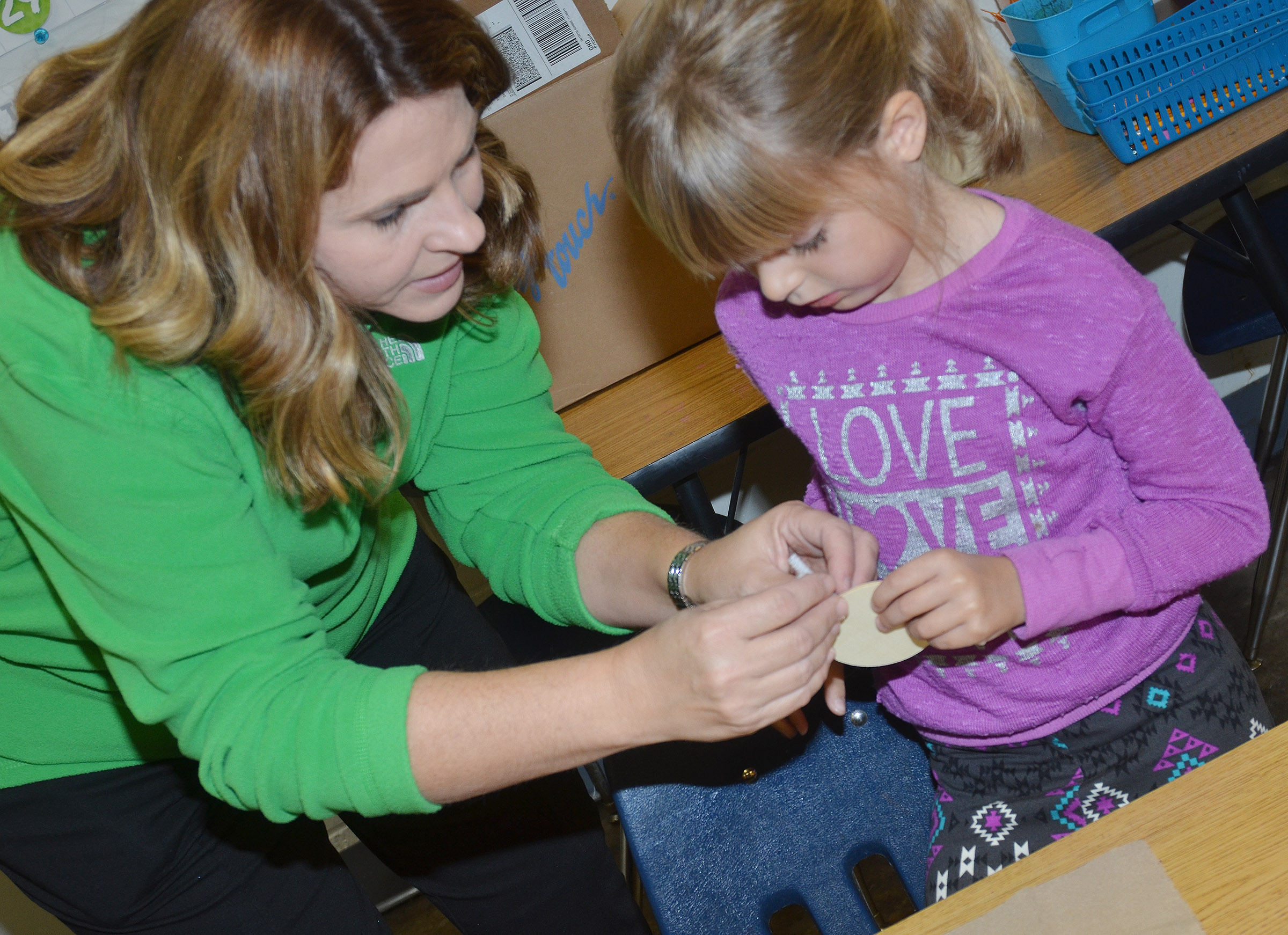 CES Guidance Counselor Sonya Orberson helps first-grader Madison Wilhoite add antlers to her reindeer ornament.