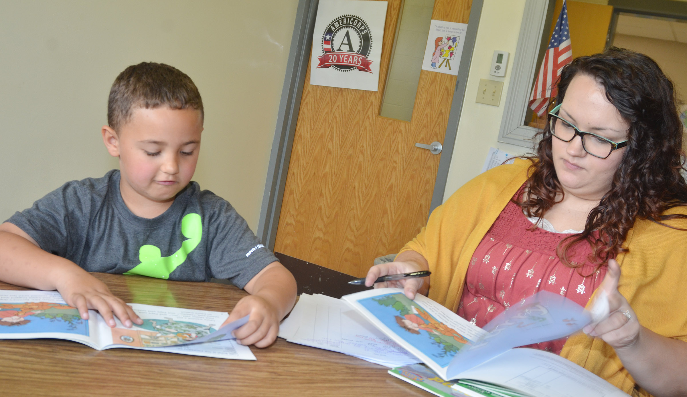 CES AmeriCorps reading tutor Lydia Rakes reads with first-grader Marion Mann.