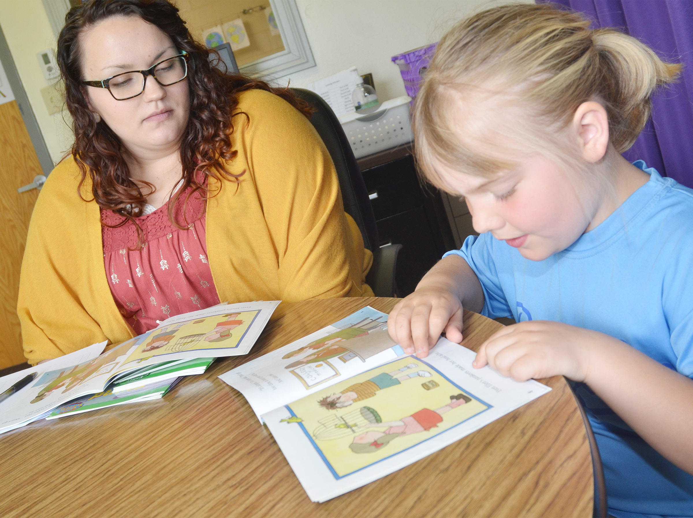 CES AmeriCorps reading tutor Lydia Rakes reads with first-grader Addysen England.