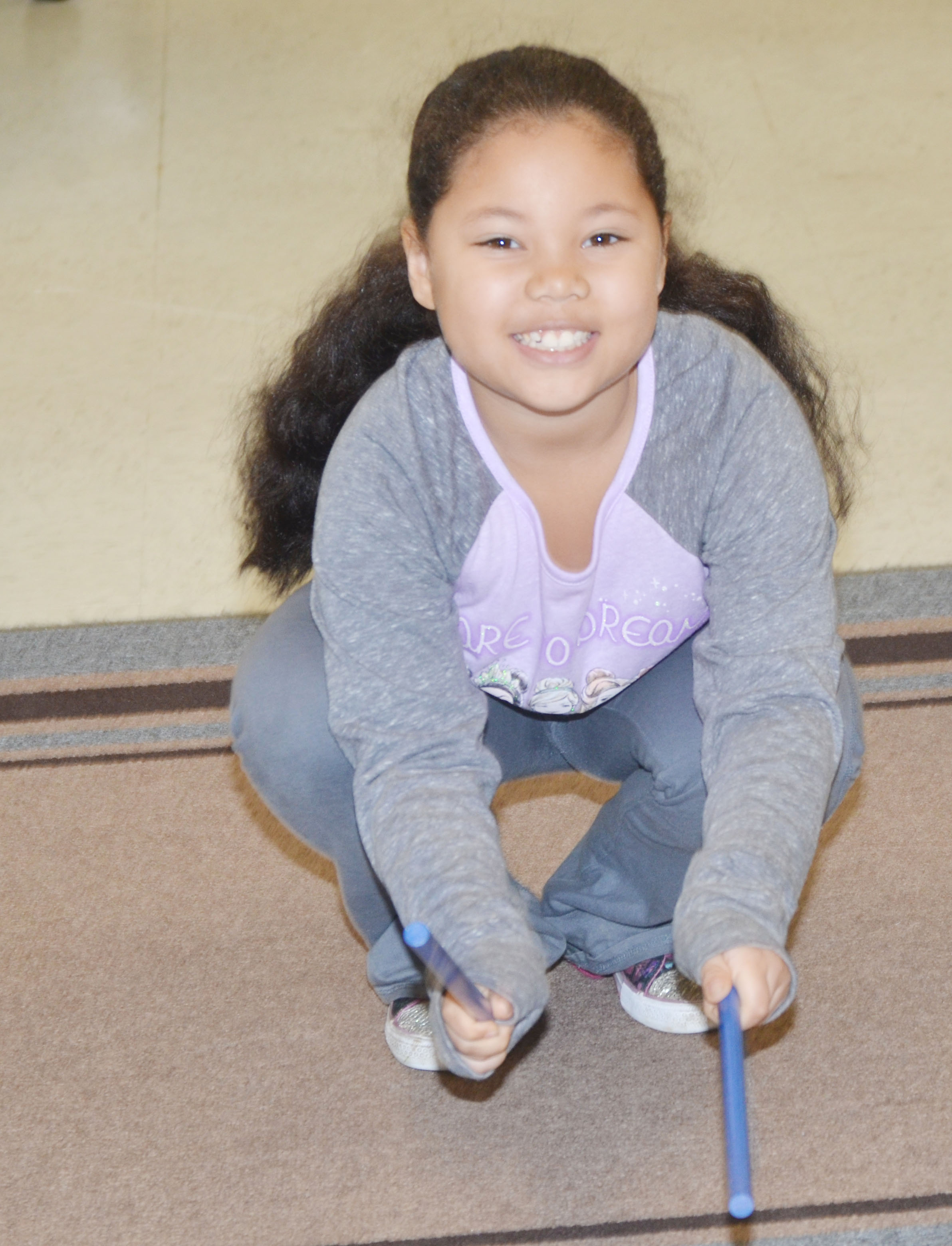 CES first-grader Briana Wooley plays the rhythm sticks.