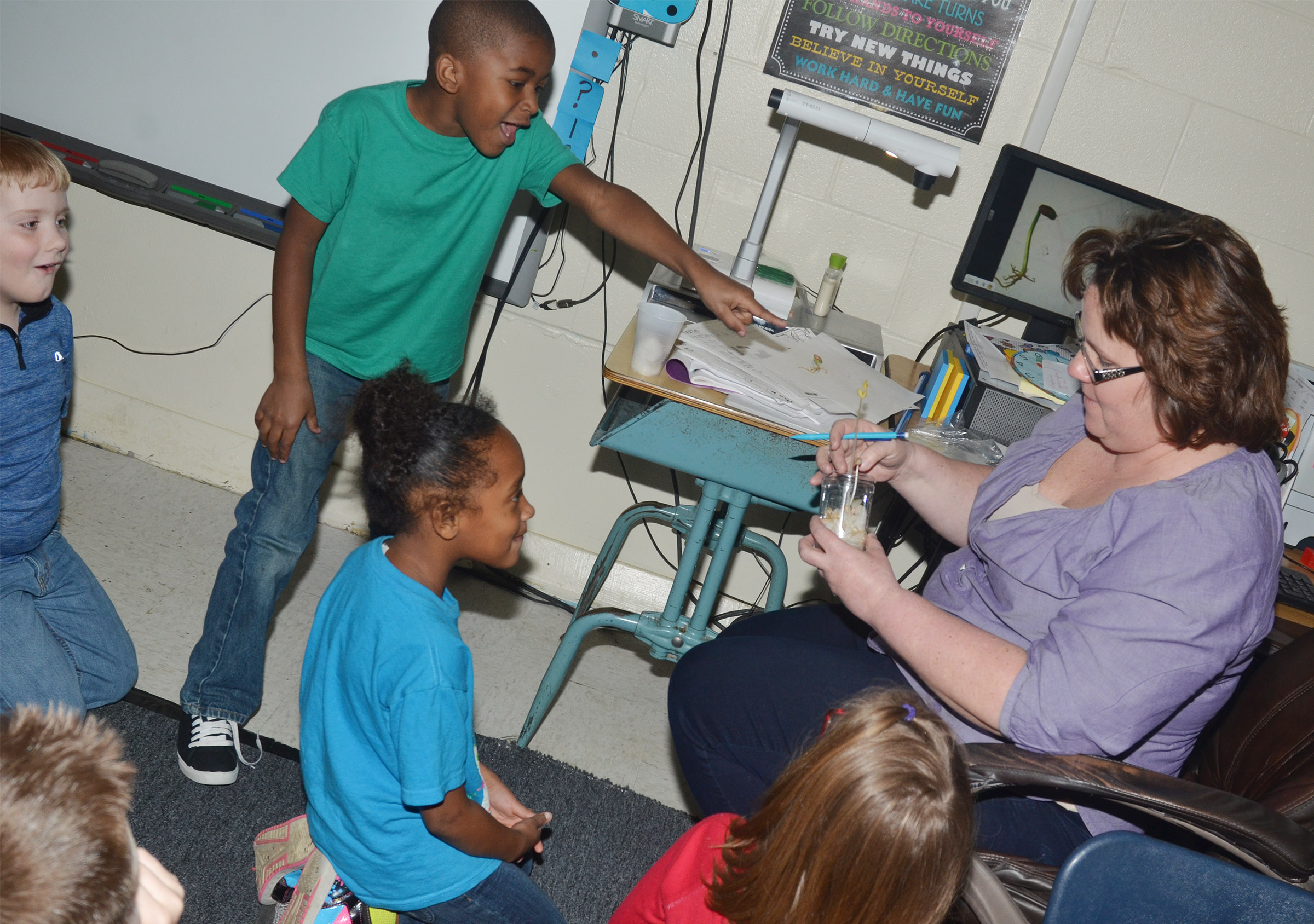 CES second-grade teacher Tracey Rinehart shows her students how much one of their bean plants has grown. From left are Aidan Bowles, Kae'vin Spaulding and Lashonda Wilkinson.