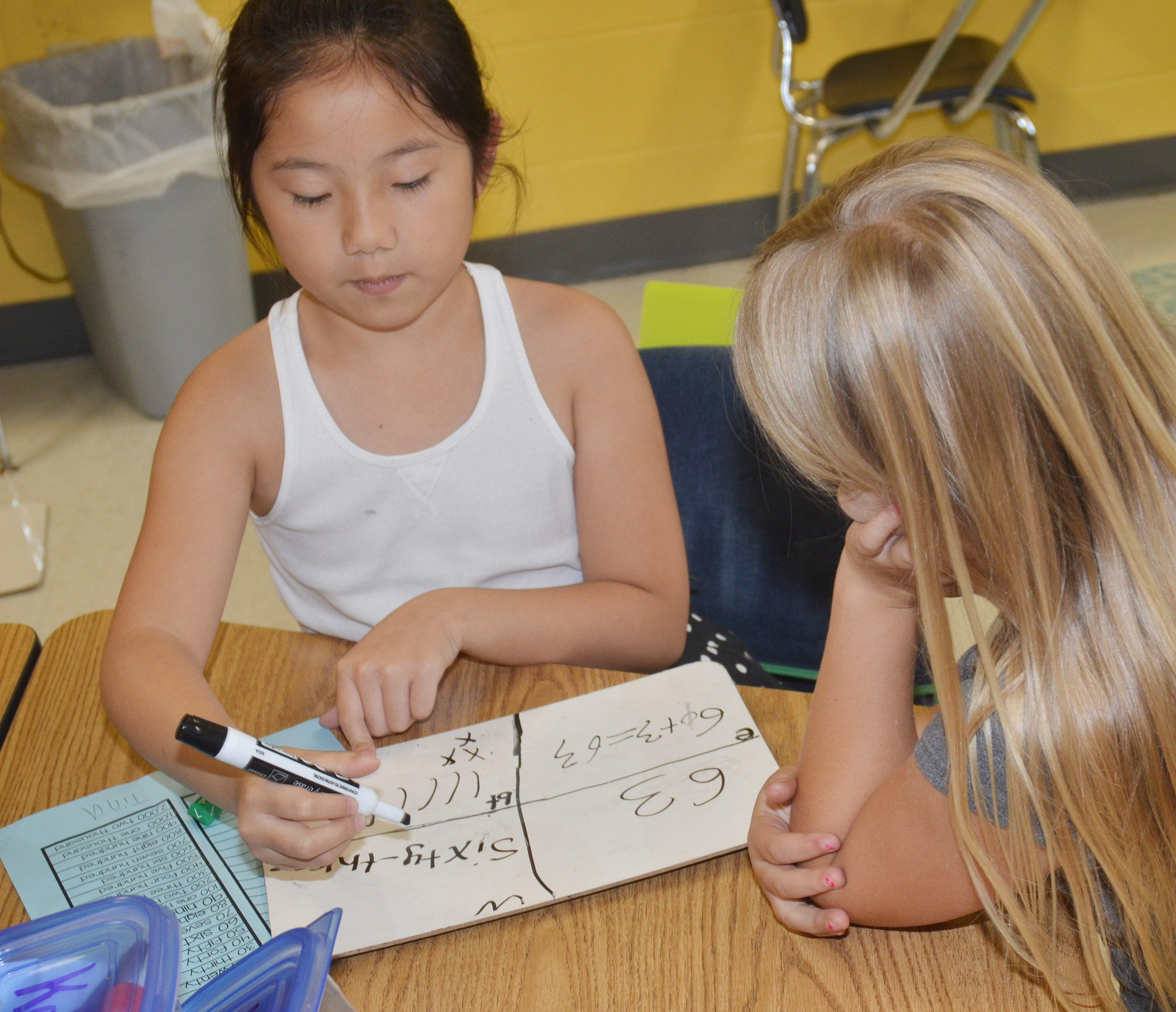 CES second-graders Tina Jiang, at left, and Asia Singleton practice writing numbers in base ten blocks.