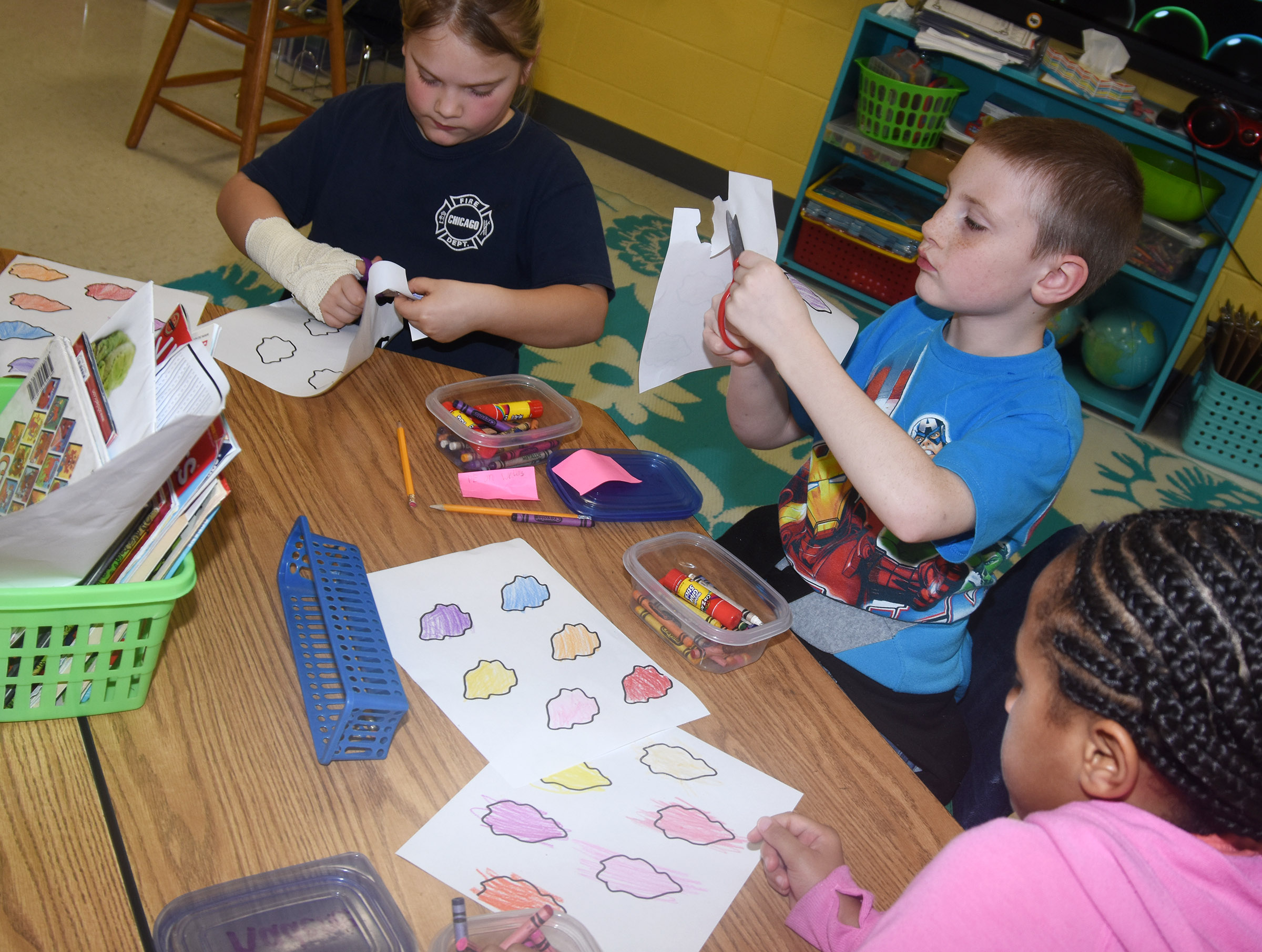 From left, CES second-graders Addysen England, James Brunner and Kadance Ford cut out their paint splotches as they create their prefix palates.