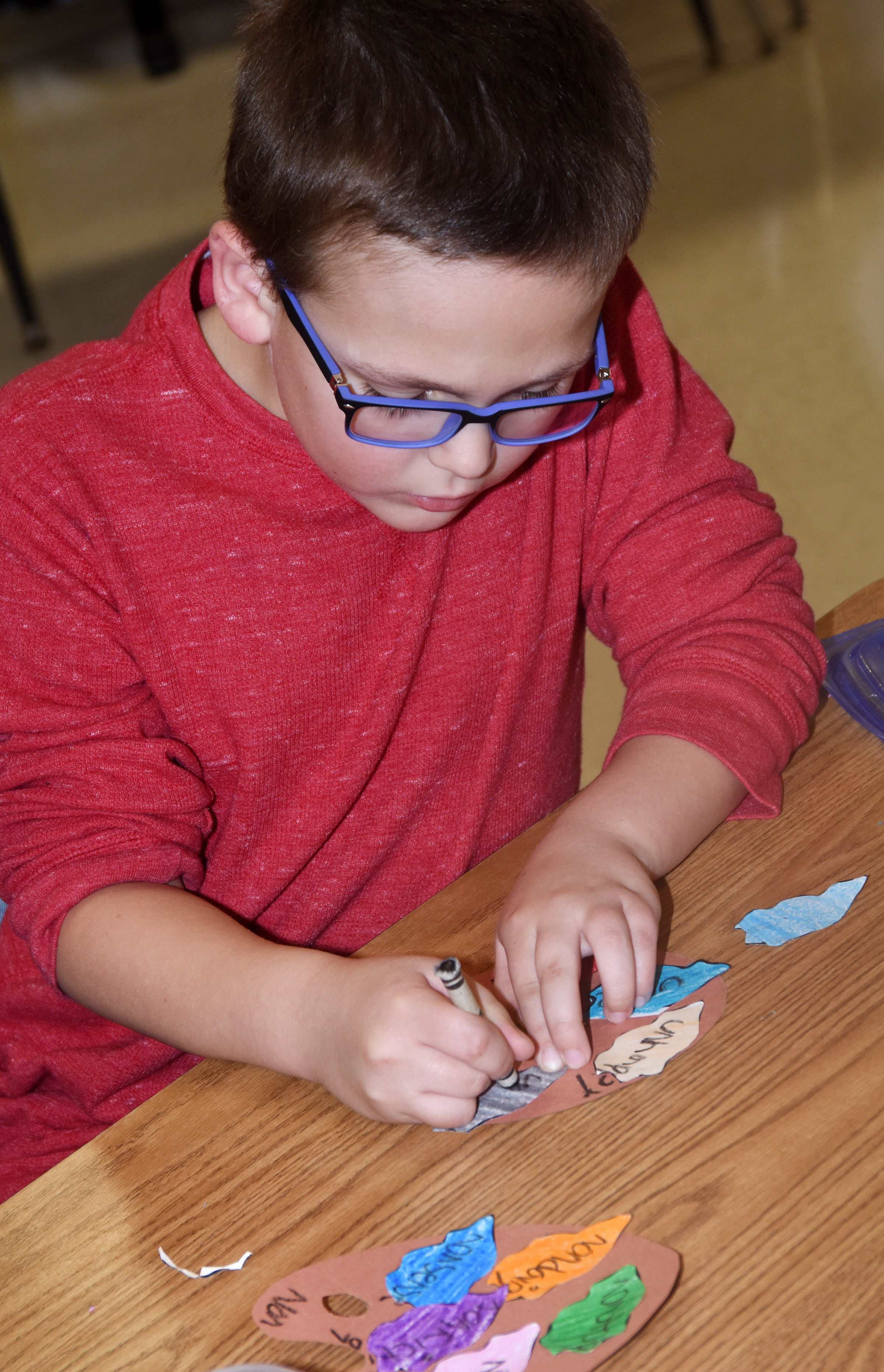 CES second-grader Brendan Martin writes words with prefixes un- and non- on his prefix palates.
