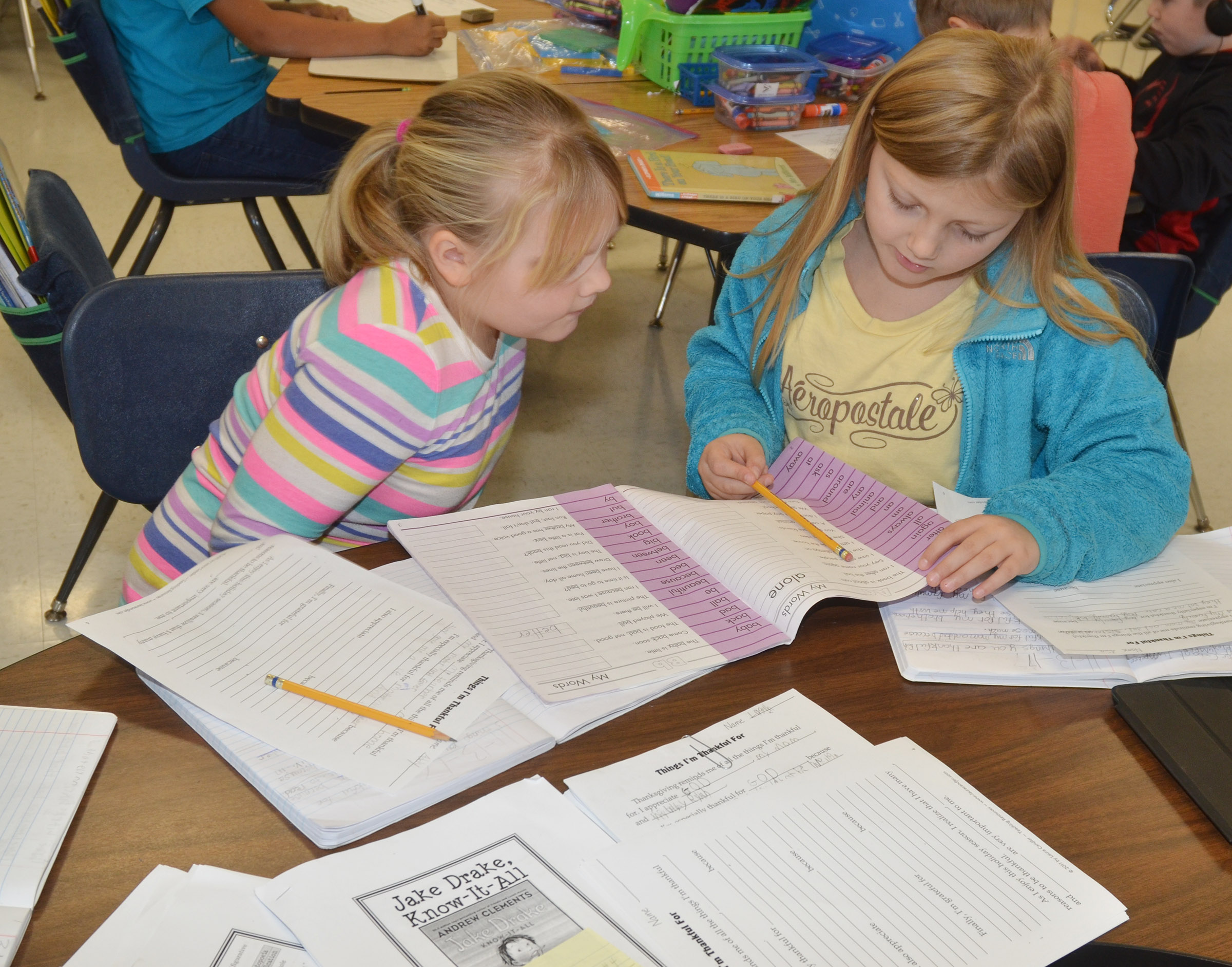 CES second-graders Addysen England, at left, and Asia Singleton work together as they write their thankful essays.