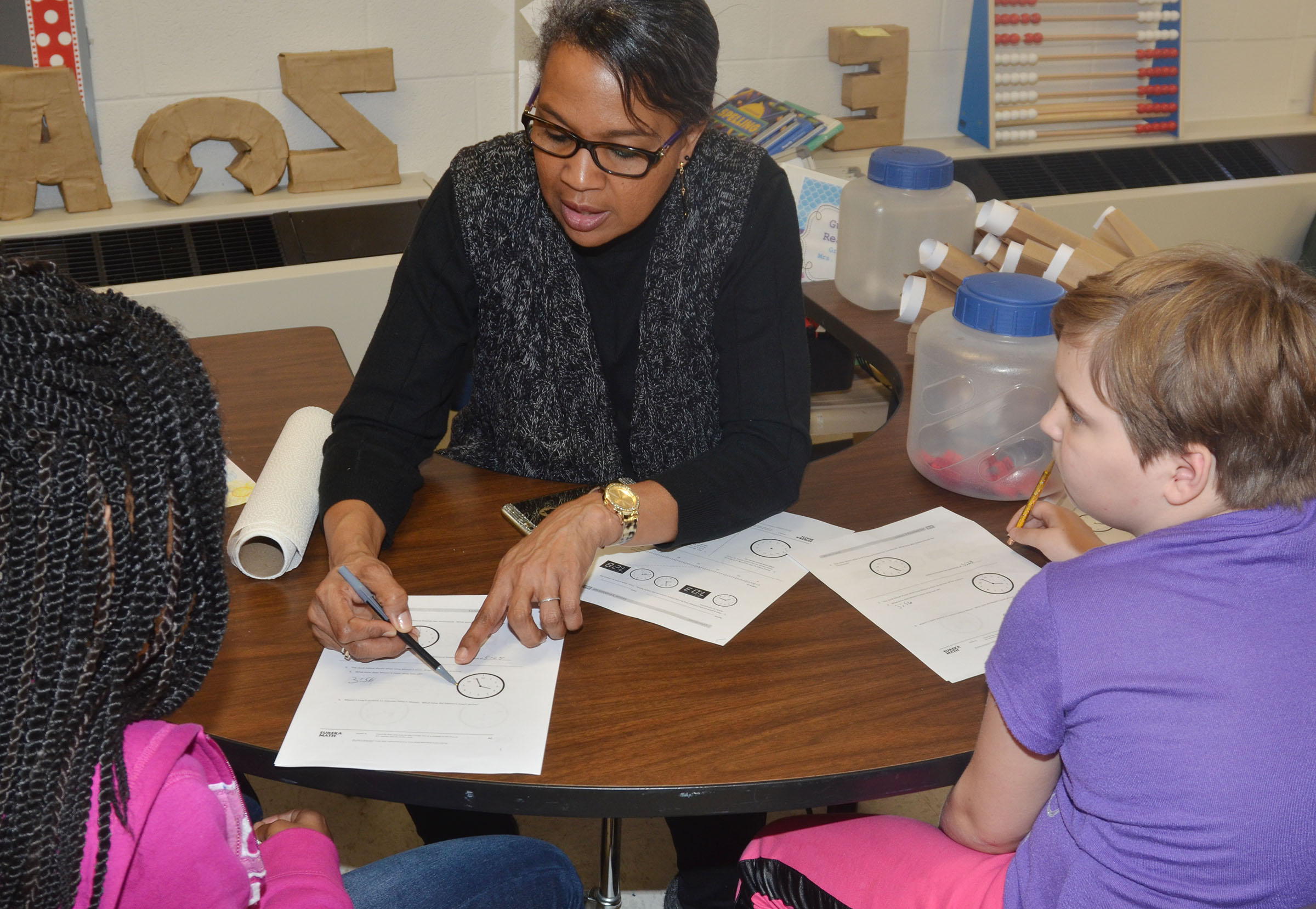 CES third-grade teacher Doretha Sanders helps Tiffani Gaddie, at left, and Mary James practice telling time.