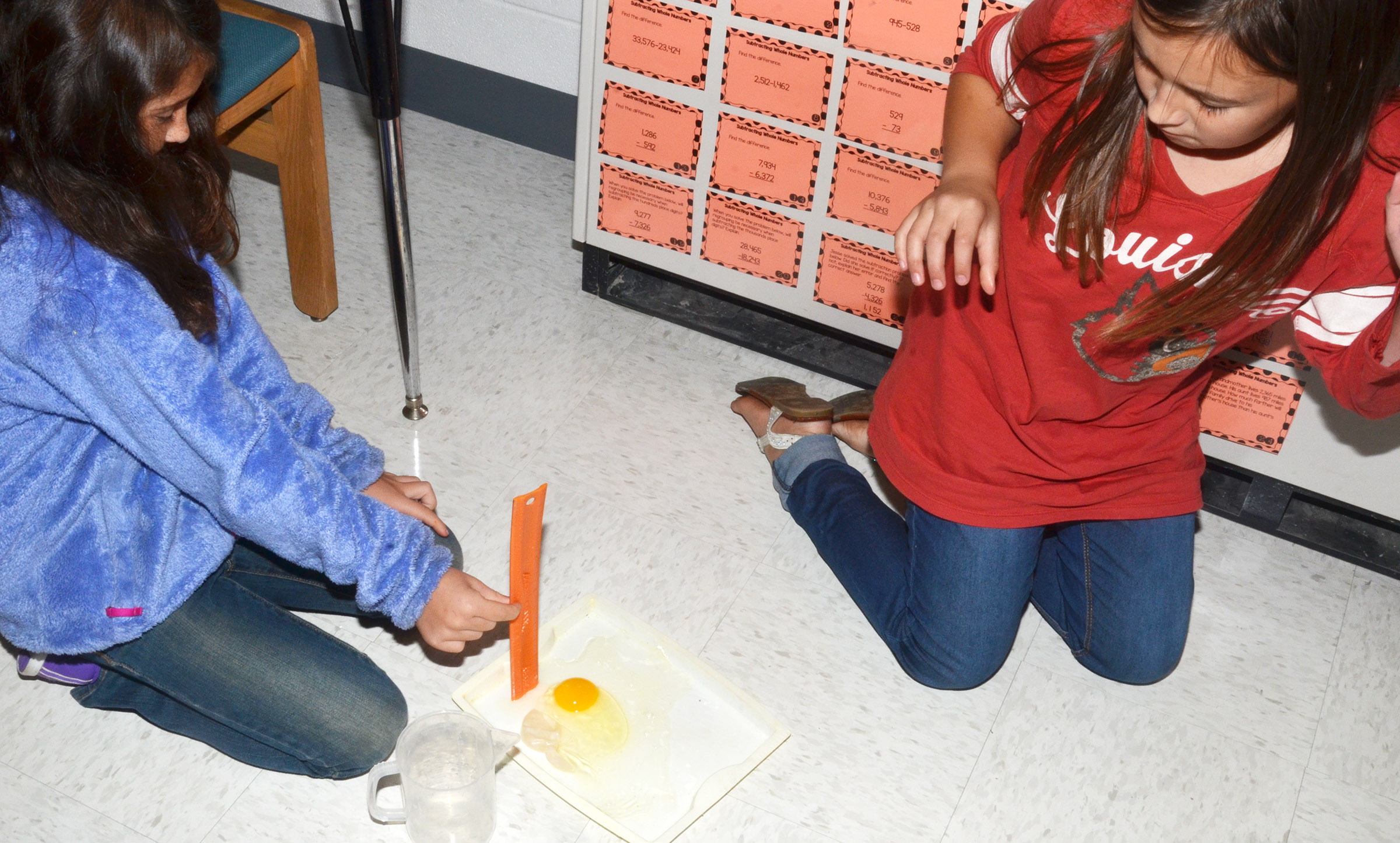 CES third-graders Ava Taylor, at left, and Annabelle Brockman drop their egg.