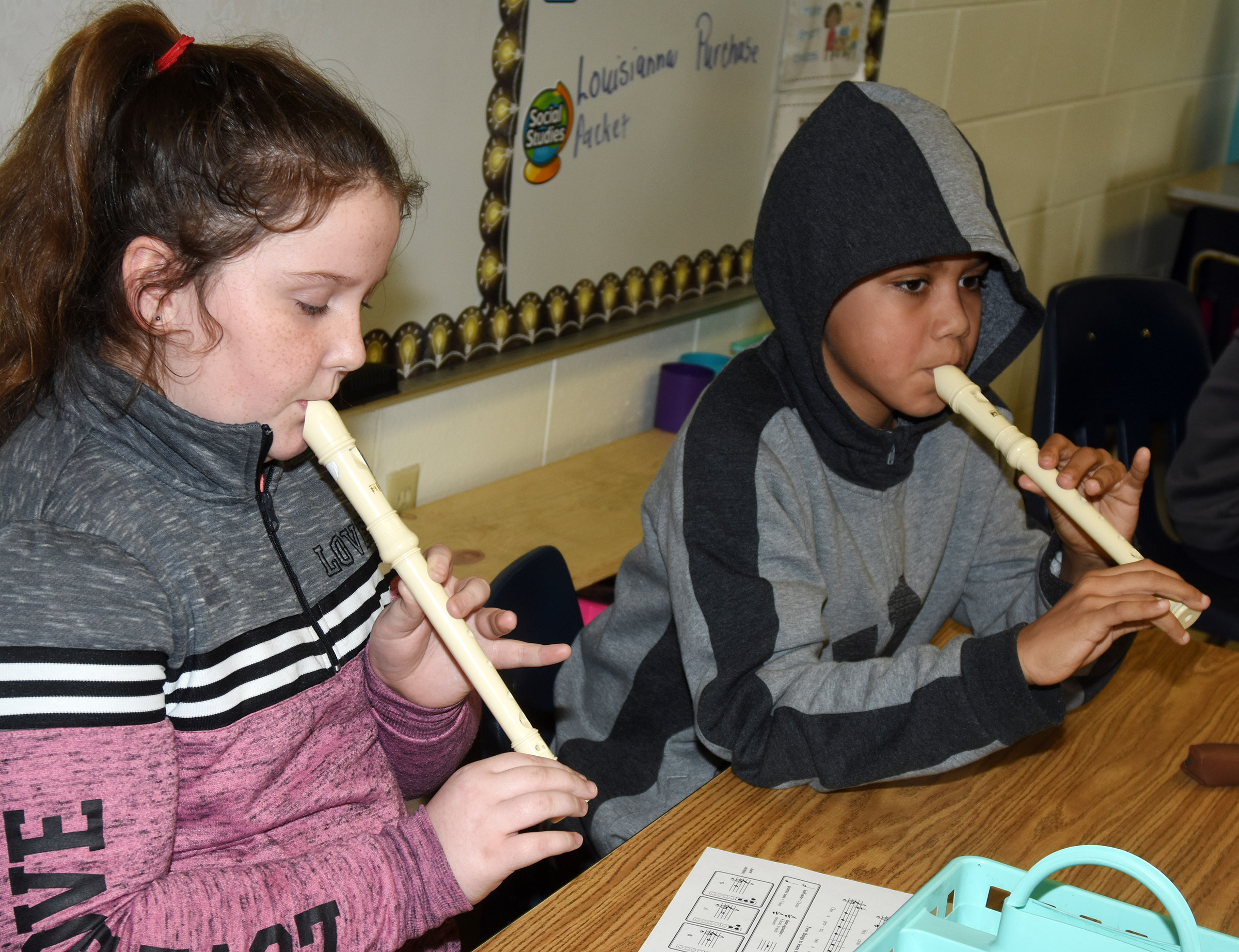 CES fourth-graders Madison Philpott, at left, and Christian Hart play Hot Cross Buns.