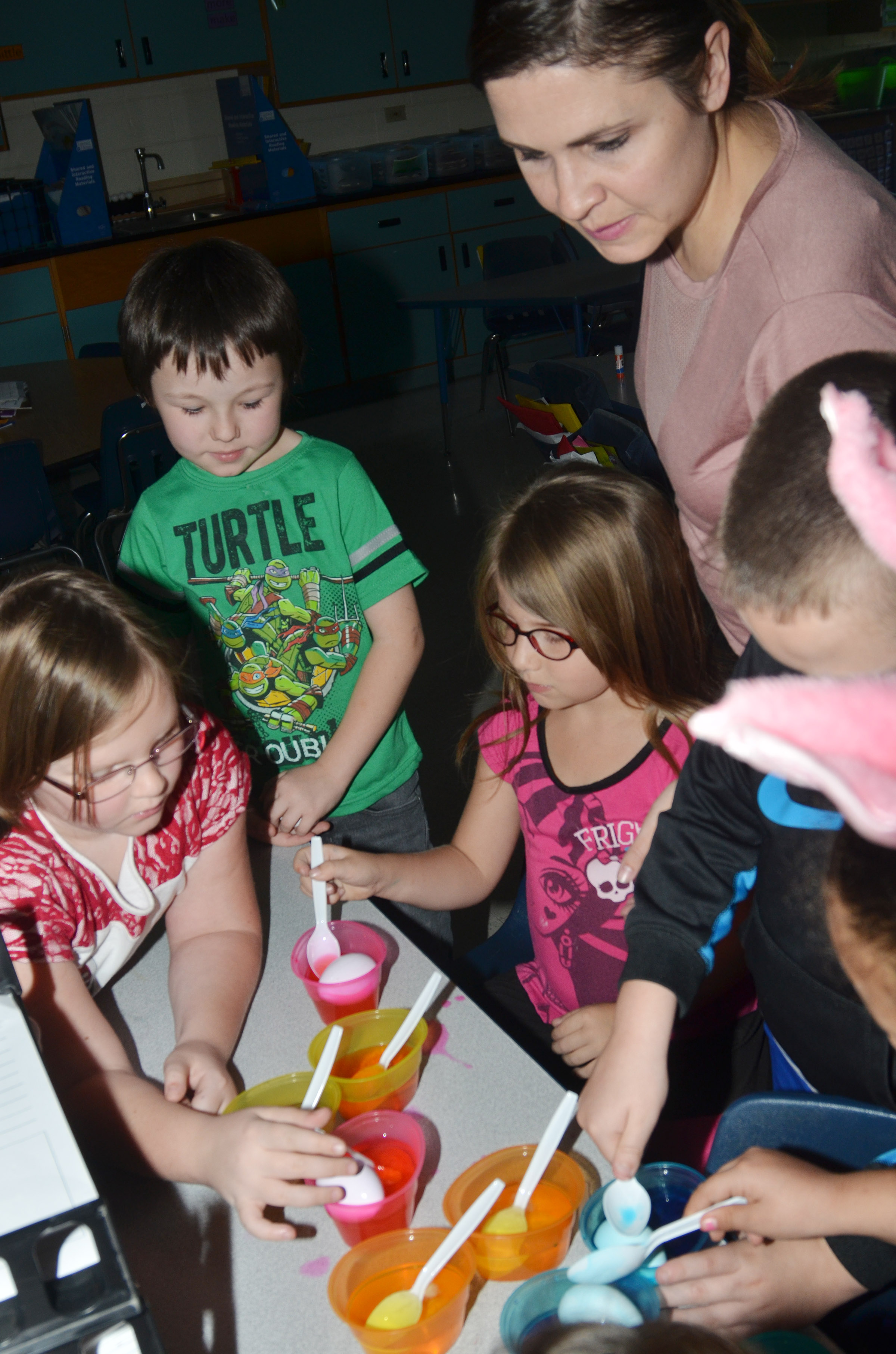 CES first-grade teacher Luci Shofner helps her students, from left, Justice Albrecht, Joseph Boudreaux and Kenady Hayes dye Easter eggs.