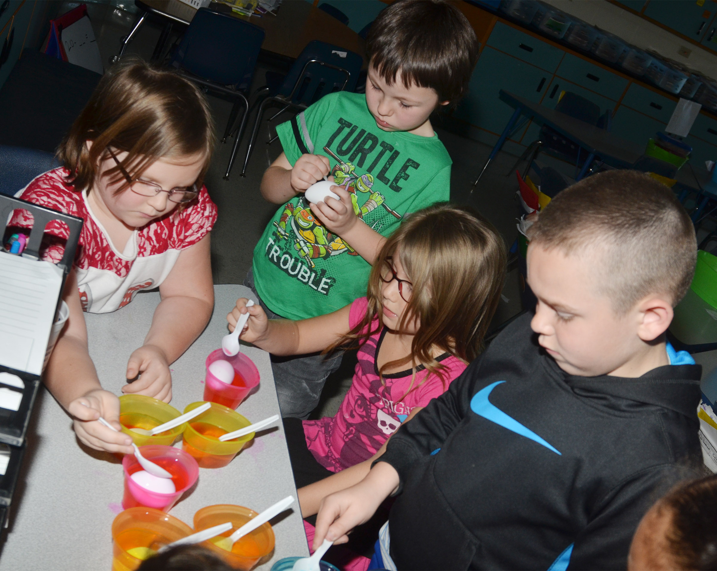 From left, CES first-graders Justice Albrecht, Joseph Boudreaux, Kenady Hayes and Colton Maggard dye their Easter eggs.