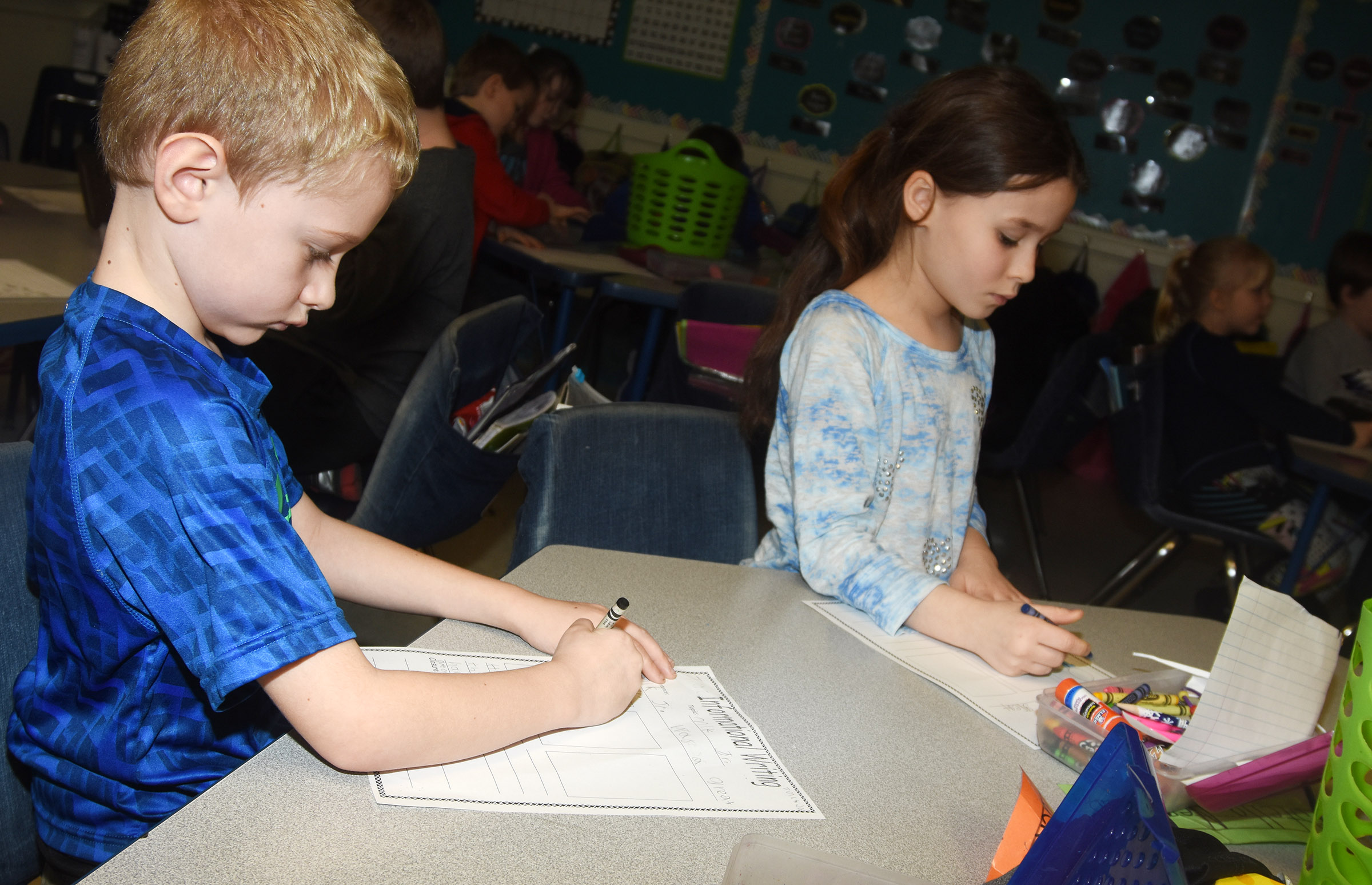 CES first-graders Jackson Wright, at left, and Stella Newcomb write about Dr. Martin Luther King Jr.