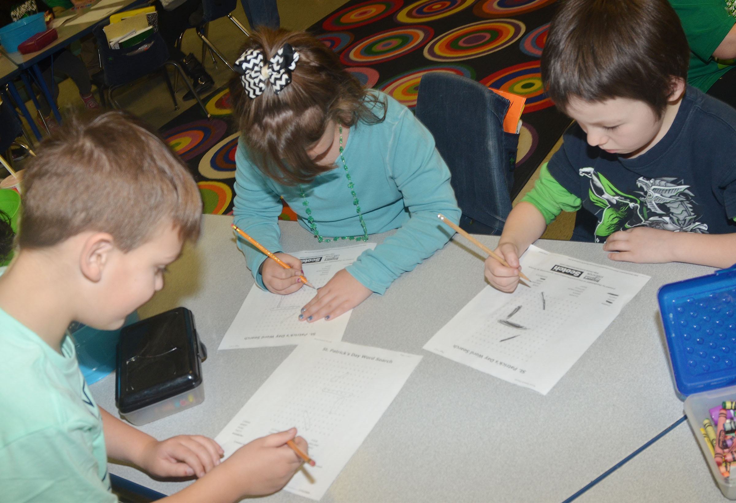 From left, CES first-graders Brendan Martin, Destiny Rhinehart and Joseph Boudreaux work a St. Patrick's Day-themed word search puzzle.
