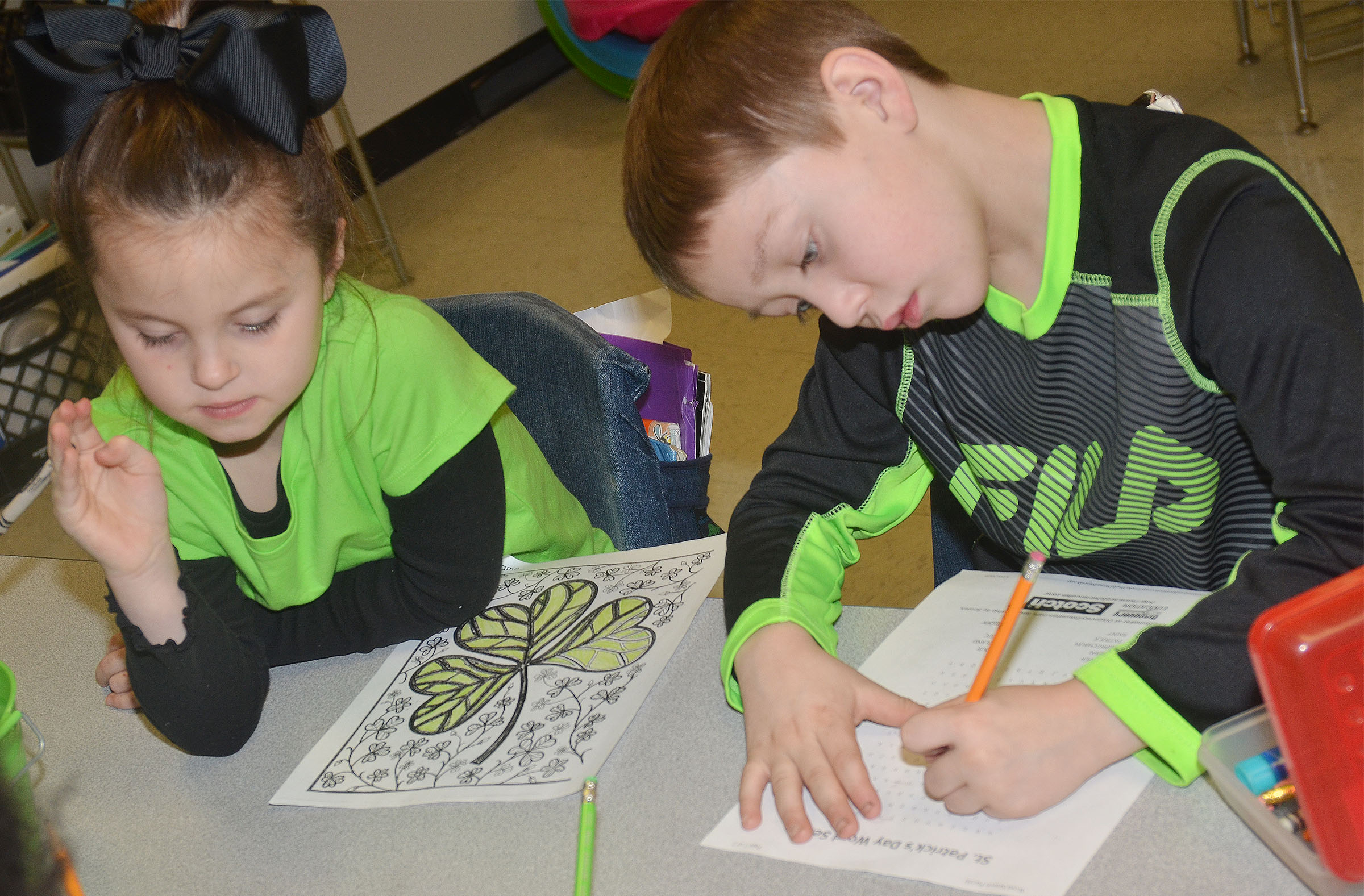 CES first-graders Molly Wolford, at left, and Jacob Golden color a shamrock and work a St. Patrick's Day-themed word search puzzle.