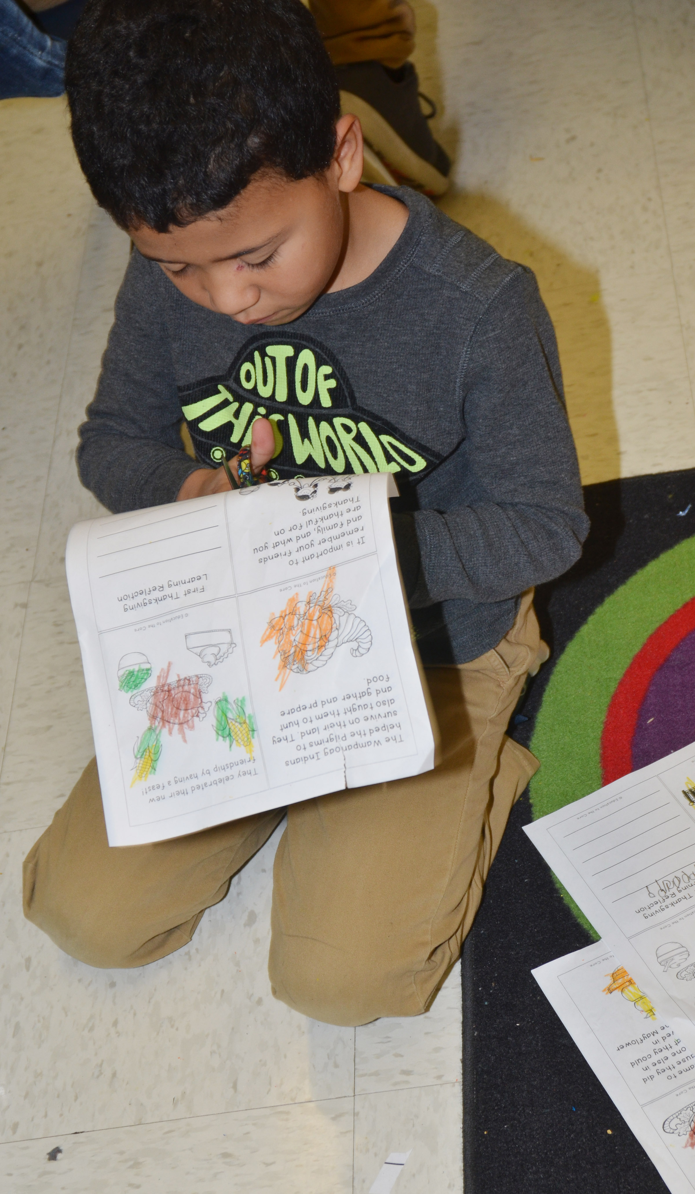 CES first-grader Ahryan Wilson cuts out his Thanksgiving book.