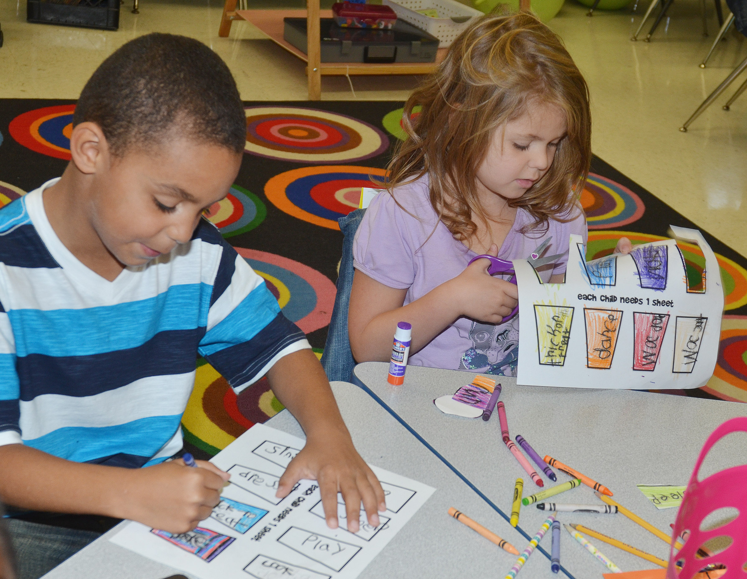 CES first-graders Quincy Travis, at left, and Aubrey Wilson color and cut out their verbs.