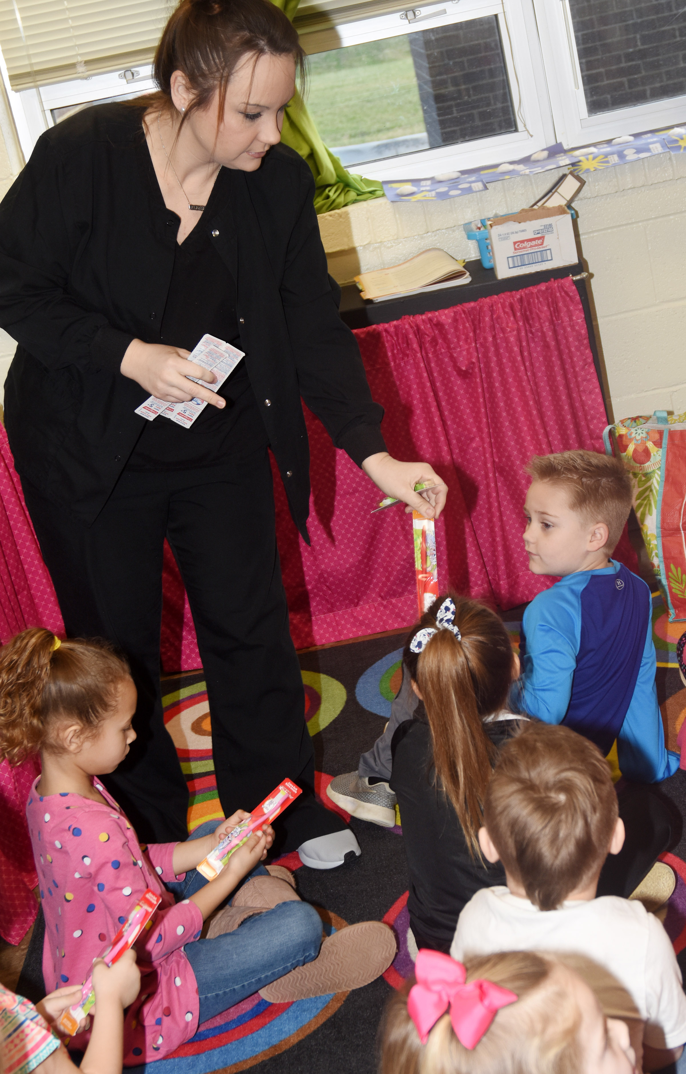 Dental hygienist Brandie Sharp, who works at Dr. John Smoot's dental office in Campbellsville, gives CES kindergarteners a new toothbrush.