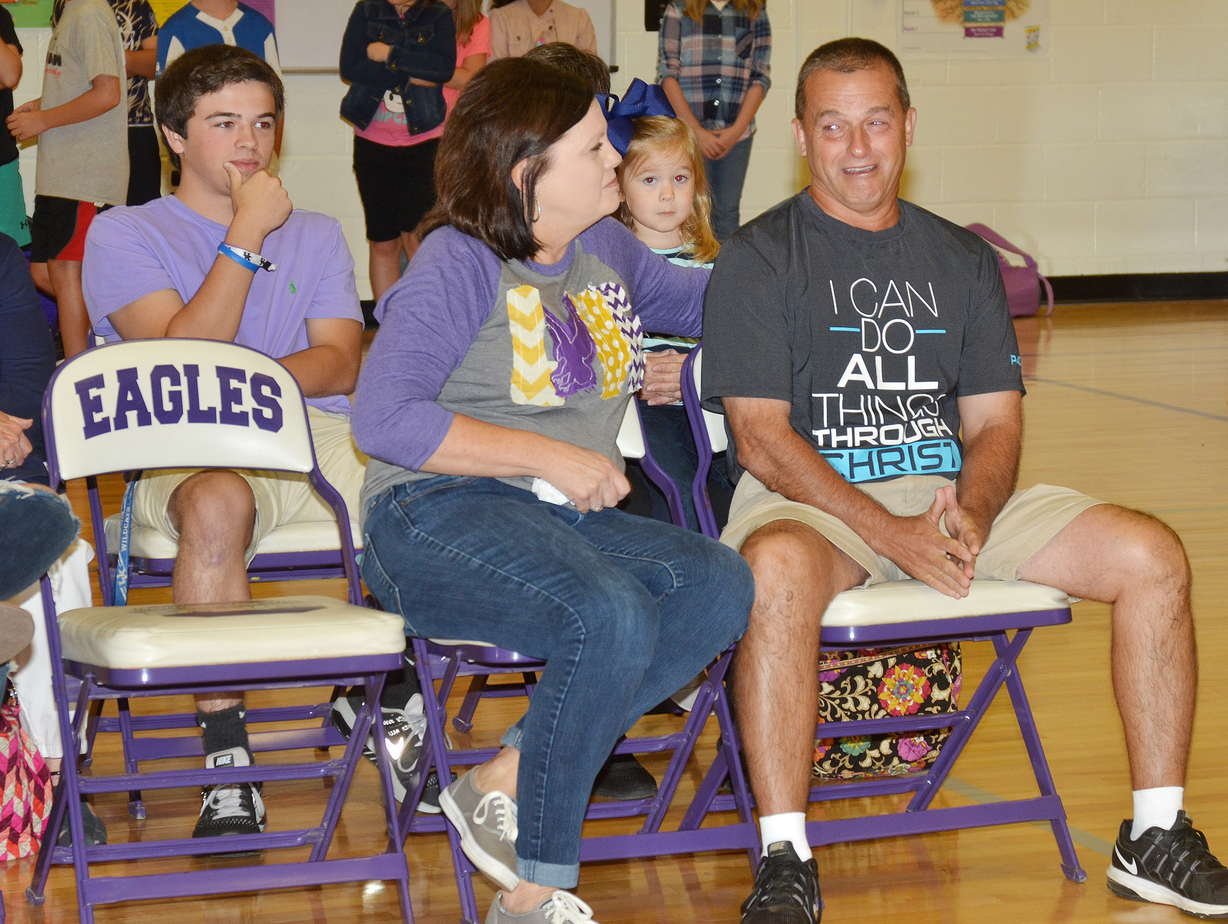 Lynn Kearney listens as students talk about what he means to them. At left is Kearney's wife, Lisa, who is a second-grade teacher at CES.