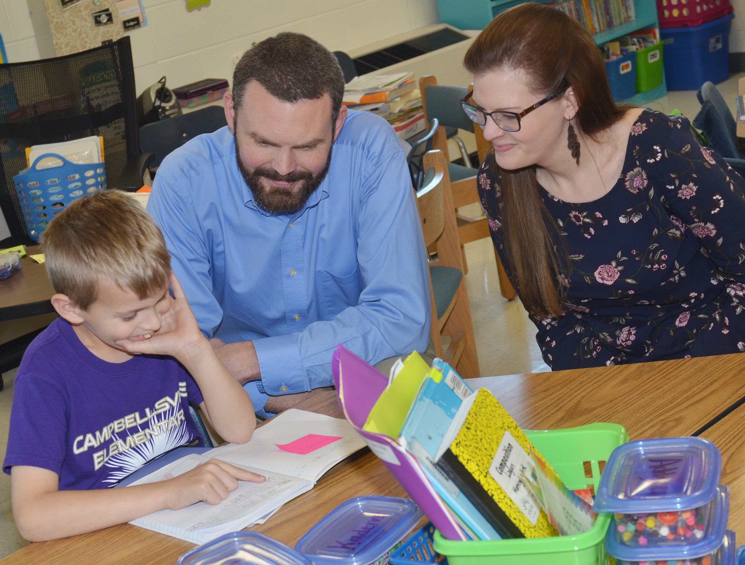 CES second-grader Logan Weddle talks to his parents John and Renae Weddle about his grades.