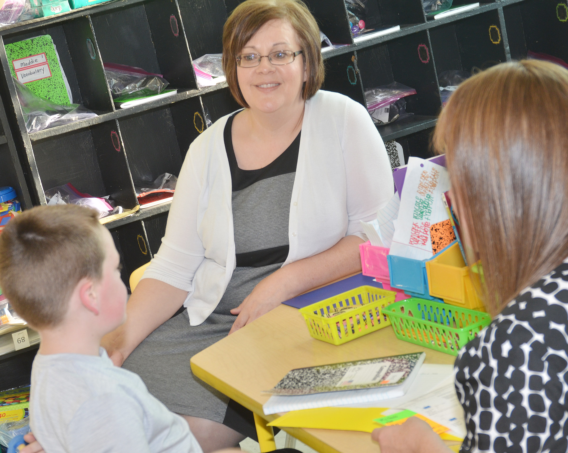 CES second-grade teacher Tonya Hagan talks to Eric Epperson and his mother Dawn Reynolds about his grades.