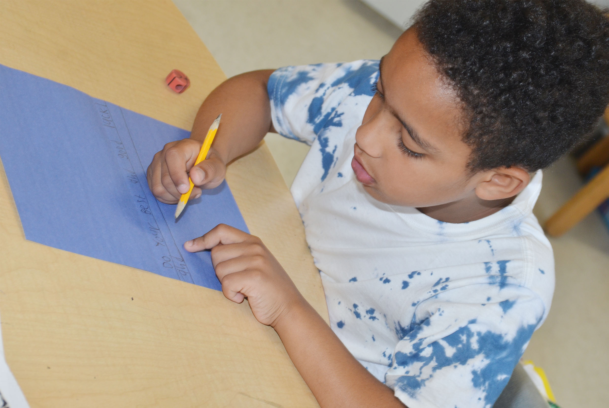 CES first-grade student Jo'van Goins makes a card for a third-grade student.