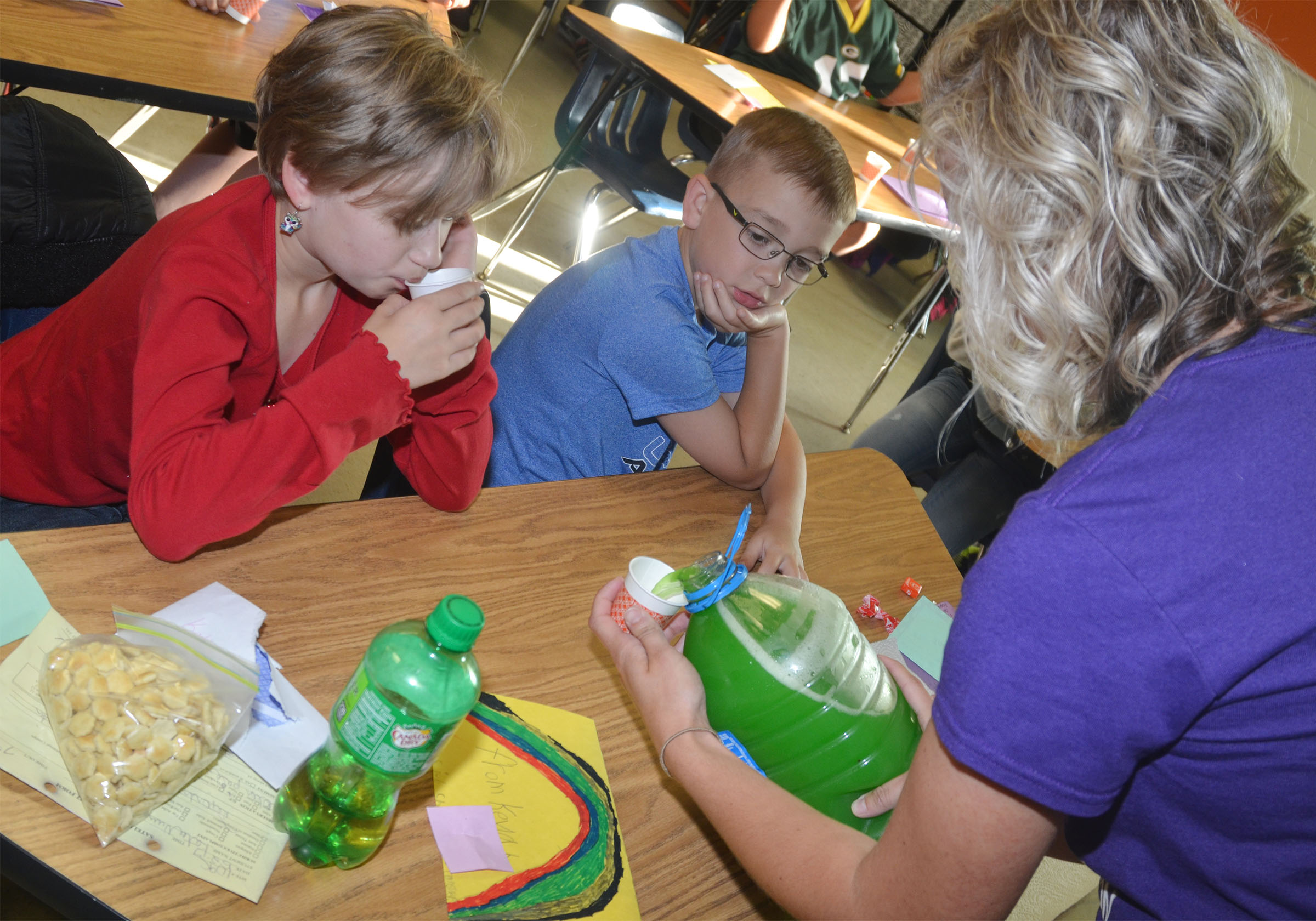 "CES third-grade teacher Hannah Jones gives students Katie Nunn, at left, and Cameron Estes their ""brain juice."""