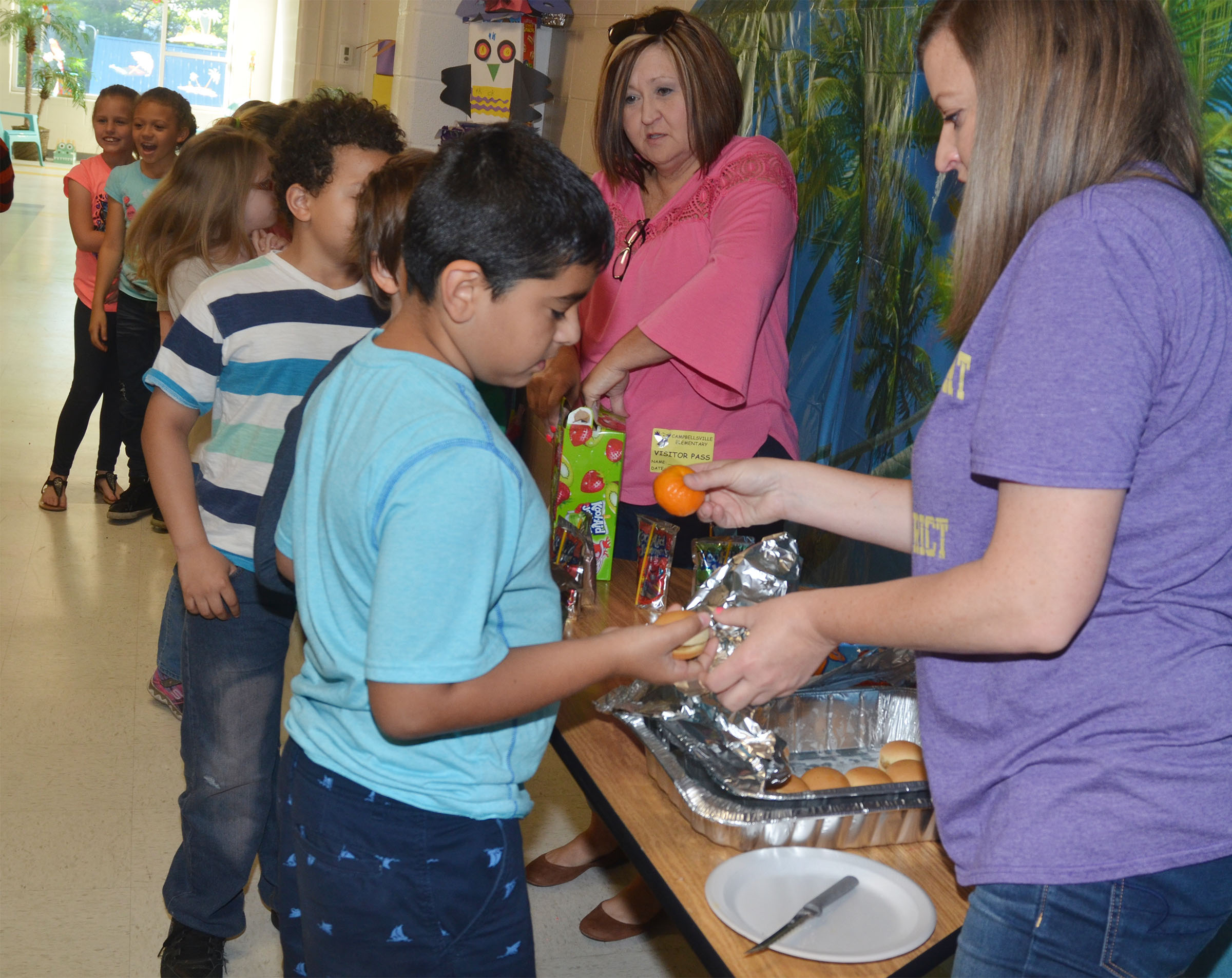 CES students are treated to a special breakfast. Serving are, at left, former kindergarten assistant Leah Levi and third-grade teacher Ashlee Petett.