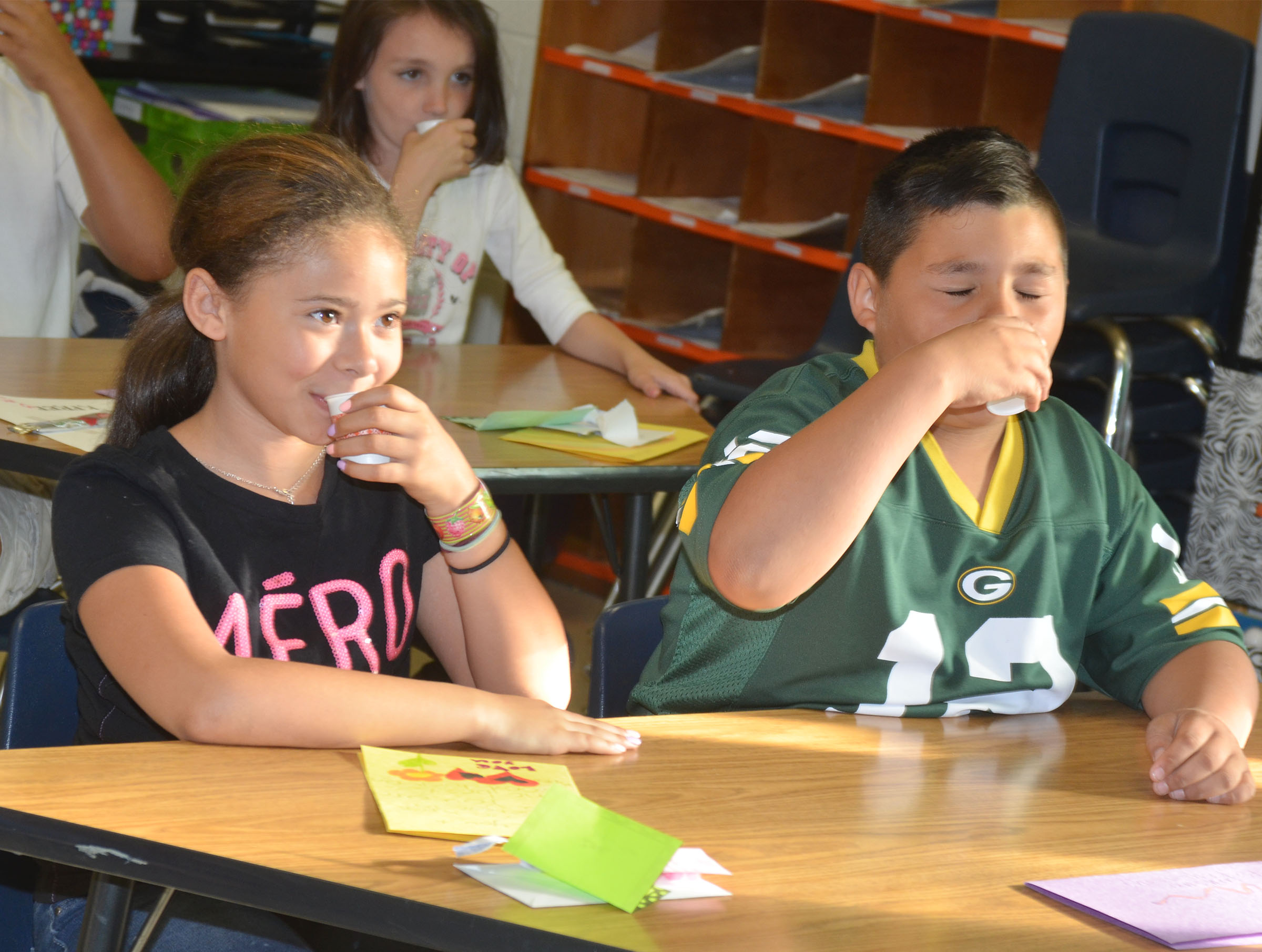"CES third-graders Rihanna Anderson, at left, and Brayden Paiz drink their ""brain juice."""