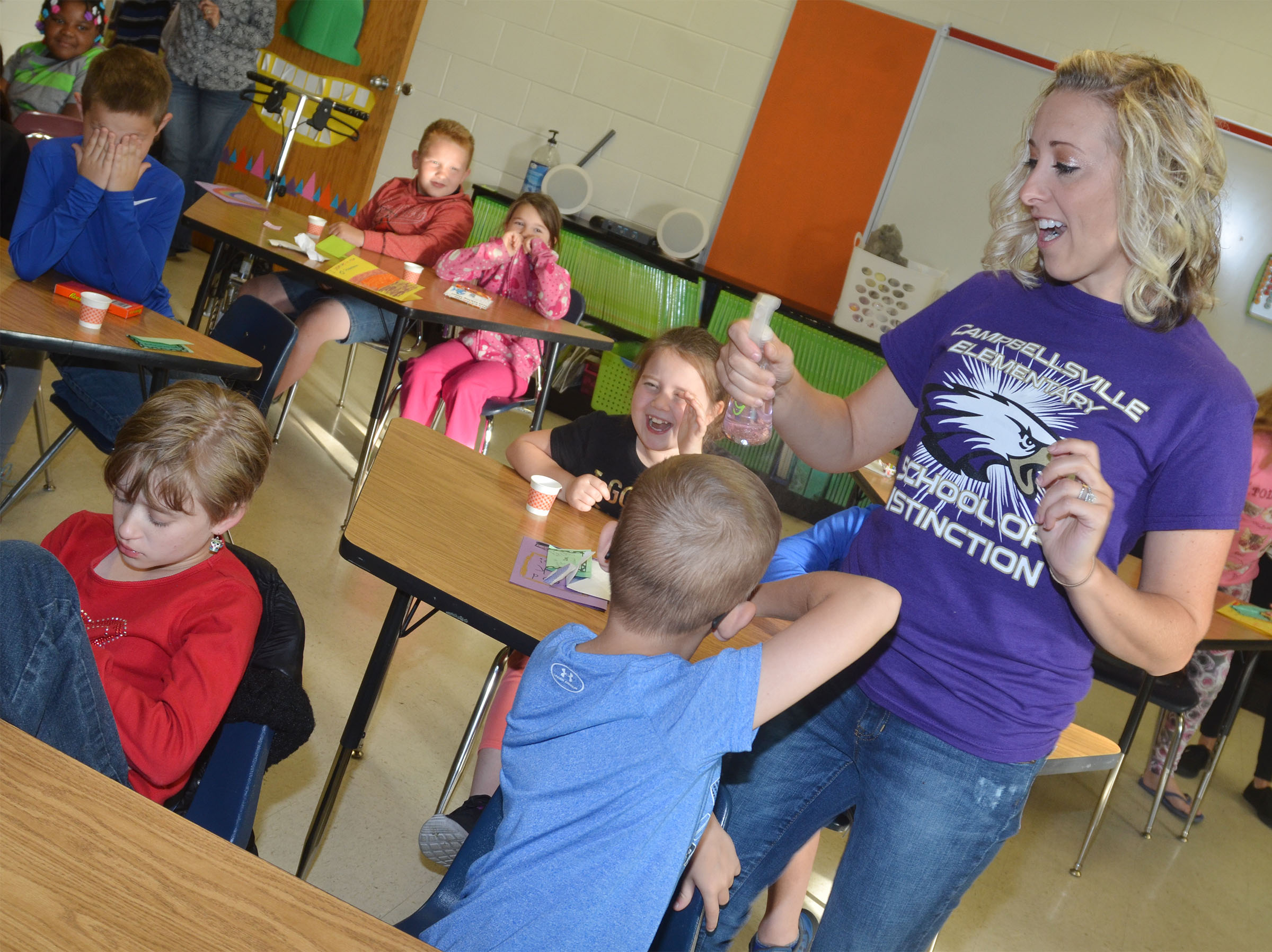 "CES third-grade teacher Hannah Jones sprays Bradley Paris with ""brain spray."""
