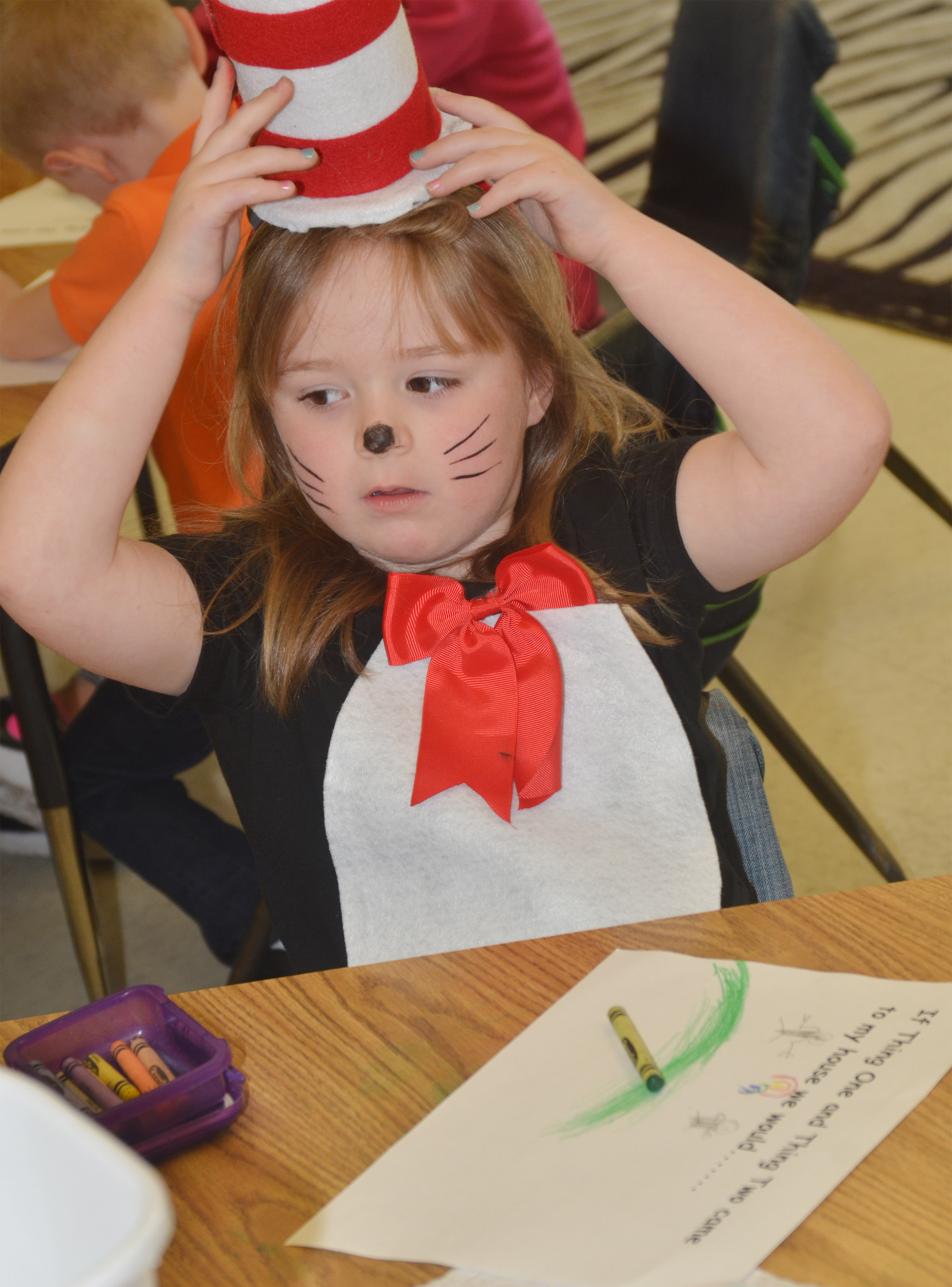 CES kindergartener Briley Sapp adjusts her Cat in the Hat hat as she writes what she would do if Thing 1 and Thing 2 visited her home.