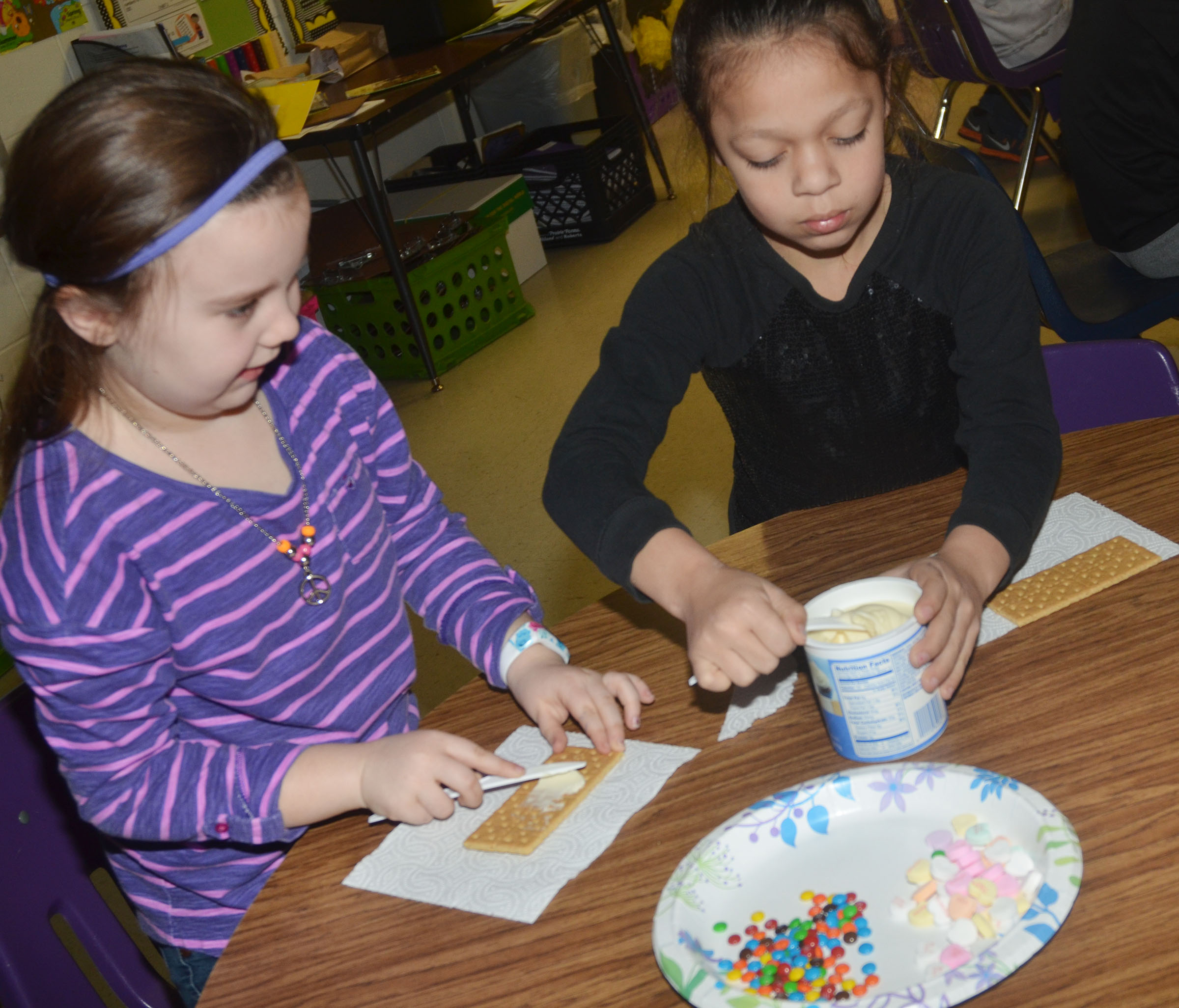 CES third-graders Maylee Wilds, at left, and Breona Bridgewater add icing to their graham crackers.