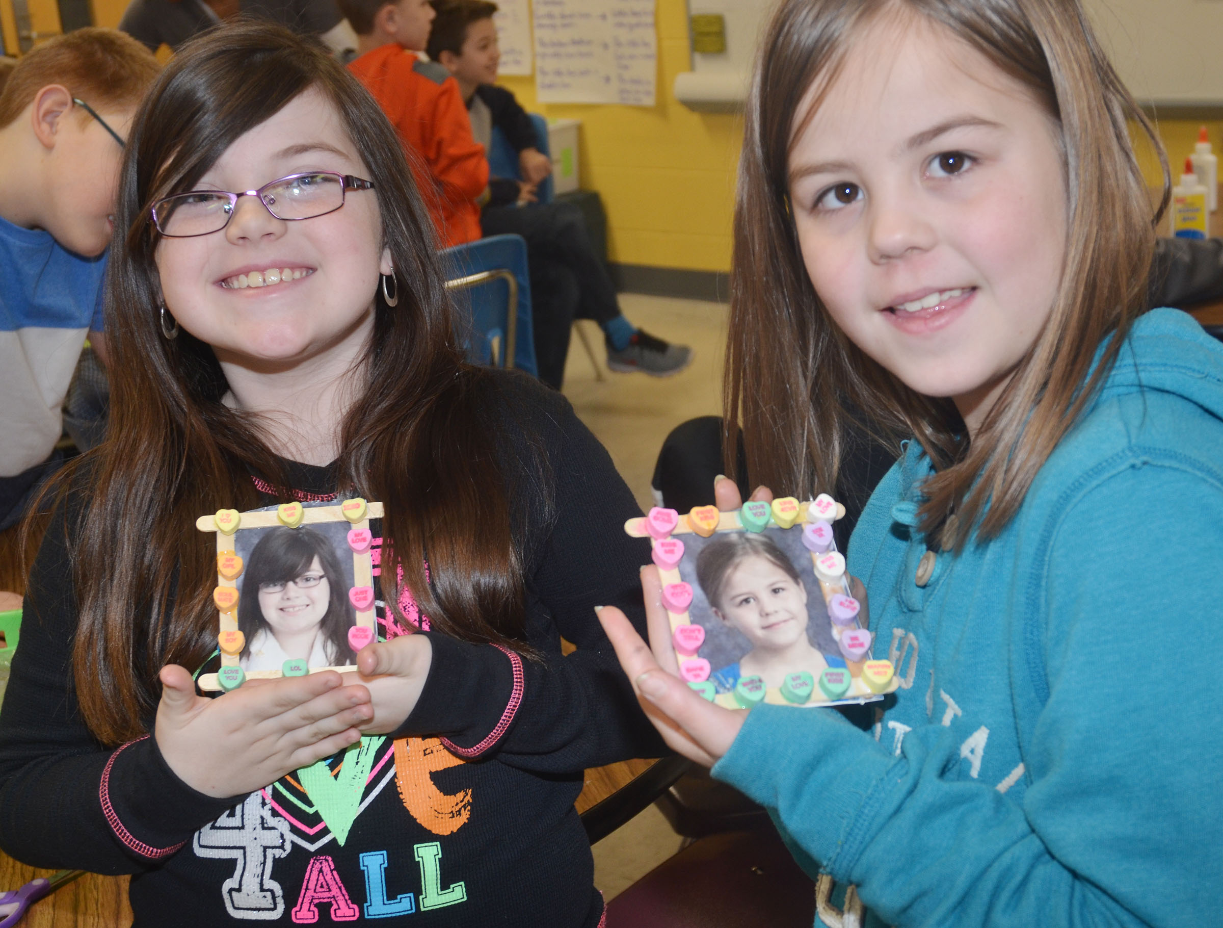 CES third-graders Lauren Pace, at left, and Chloe Bates hold their finished picture frames.