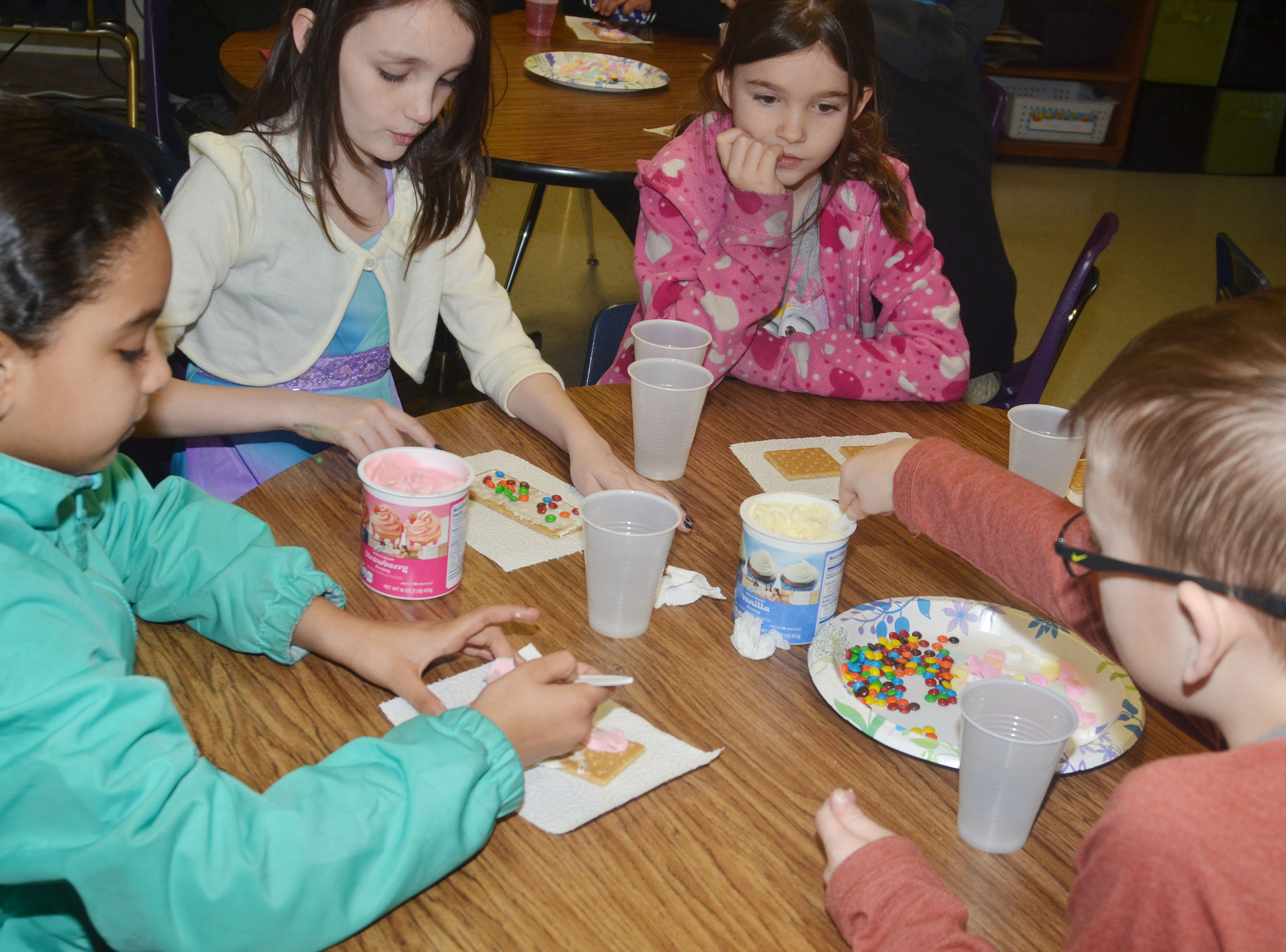 From left, CES third-graders Aleecia Knezevic, Paige Ritchie, Destiny Abell and Cameron Estes decorate their graham crackers.