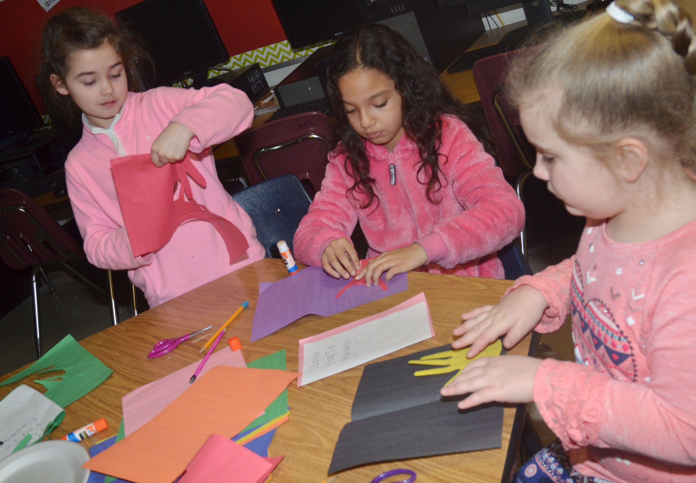 From left, CES third-graders Alexis Wolford, Alyssa Knezevic and Kiera Bailey make their Valentine cards.