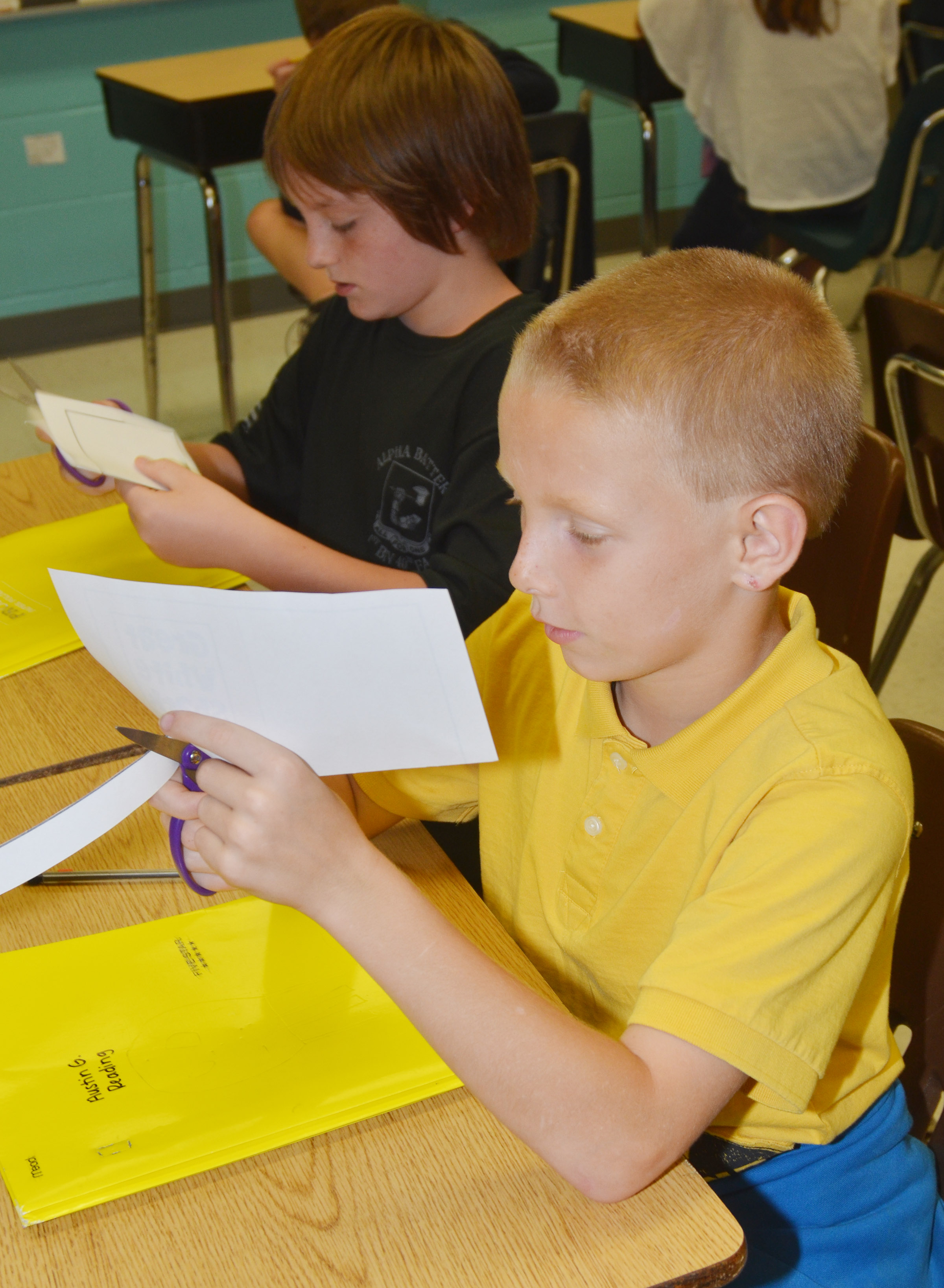 CES fifth-graders Kanan Bruce, at left, and Austin Gabbert cut out their mini-books.