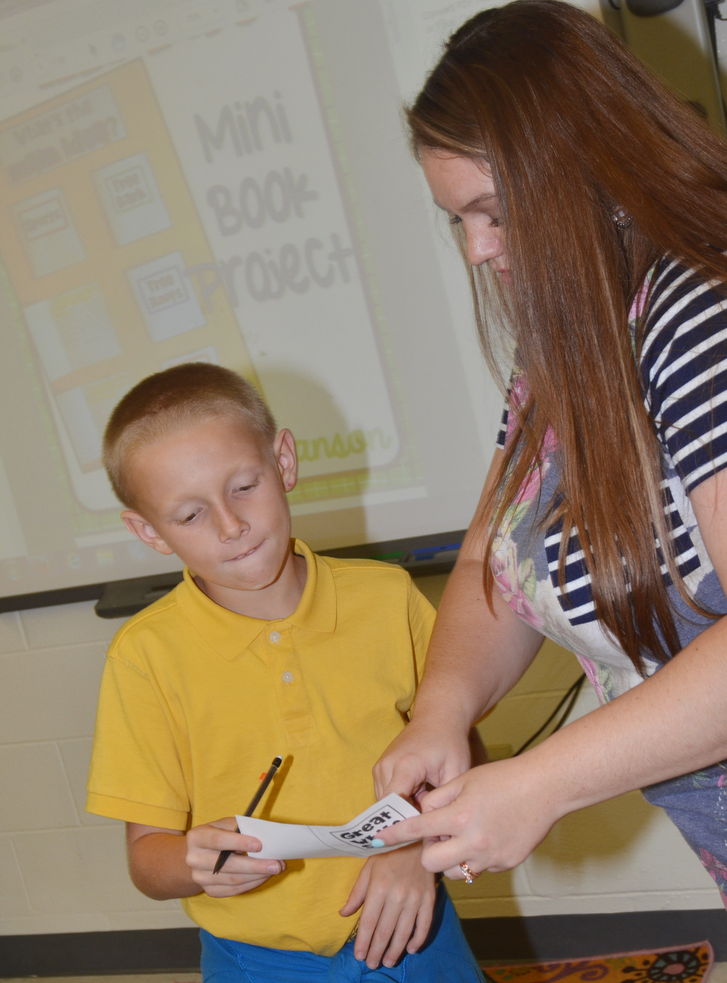 CES fifth-grade teacher Ann Michael Tucker talks to Austin Gabbert about his mini-book.