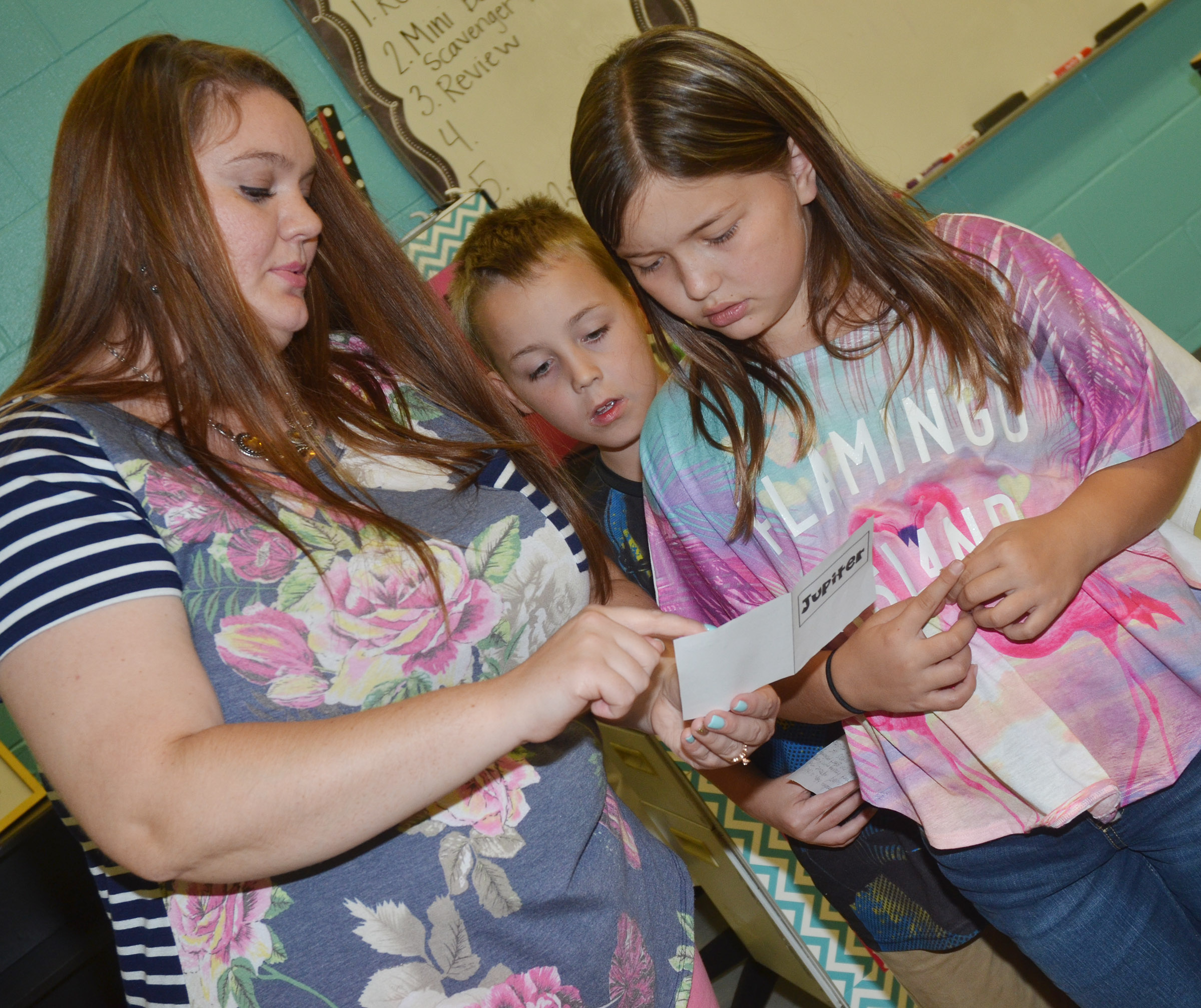 CES fifth-grade teacher Ann Michael Tucker talks to Spencer Bates, at left, and Kate Billeter about their mini-books.