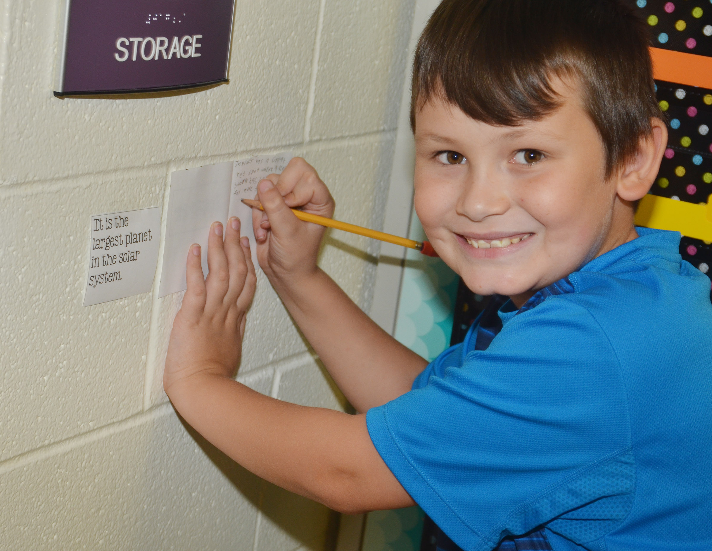 CES fifth-grader Mason Fisher writes a supporting detail in his mini-book about Jupiter.