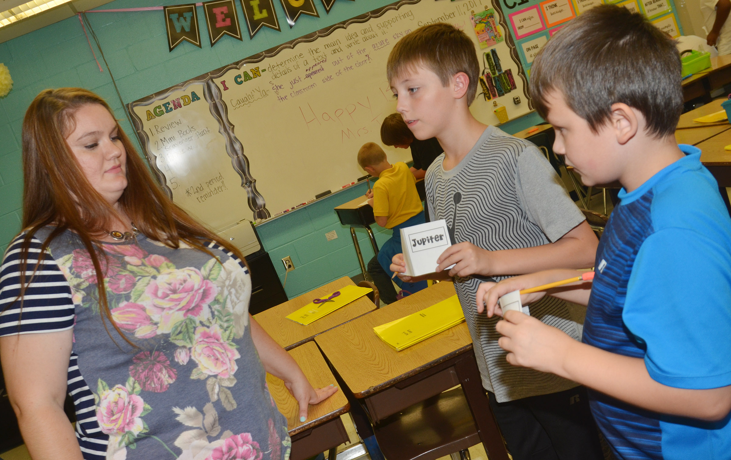 CES fifth-grade teacher Ann Michael Tucker looks at Jaxon Garrett's and Mason Fisher's mini-books.