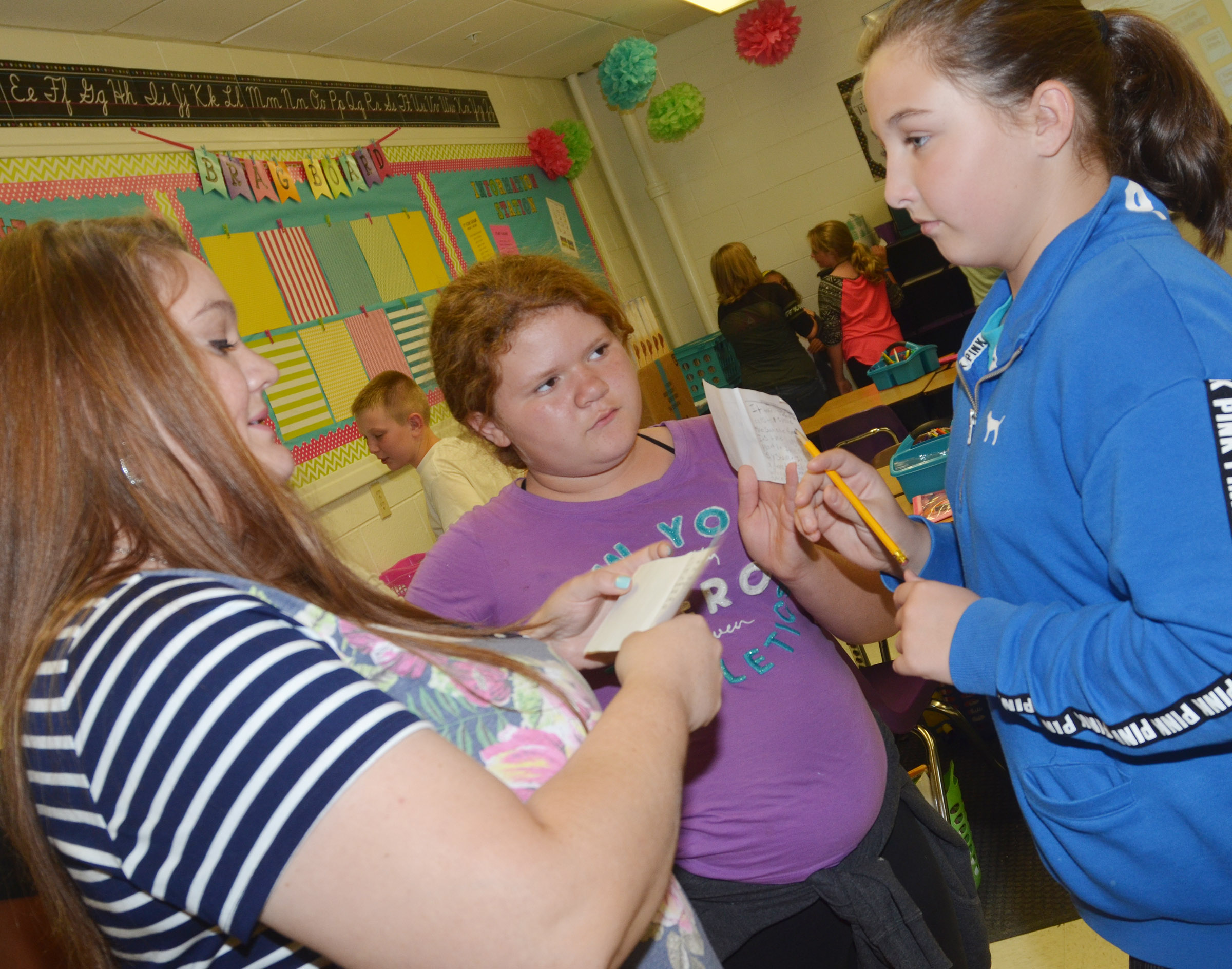 CES fifth-grade teacher Ann Michael Tucker talks to Carmen Gurley, at left, and Riley Newton about their mini-books.