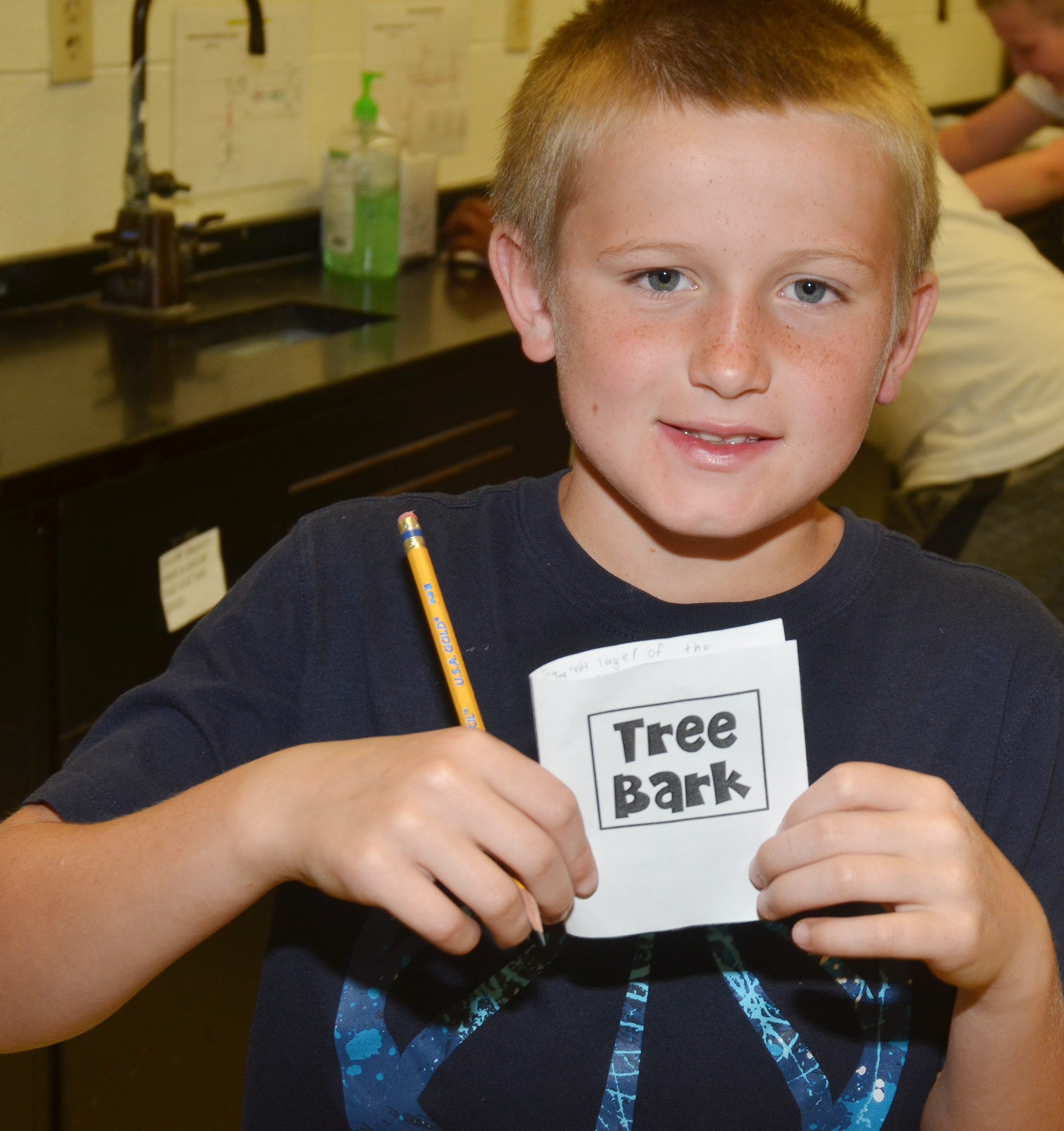 CES fifth-grader Arthur Singleton holds his mini-book about tree bark.