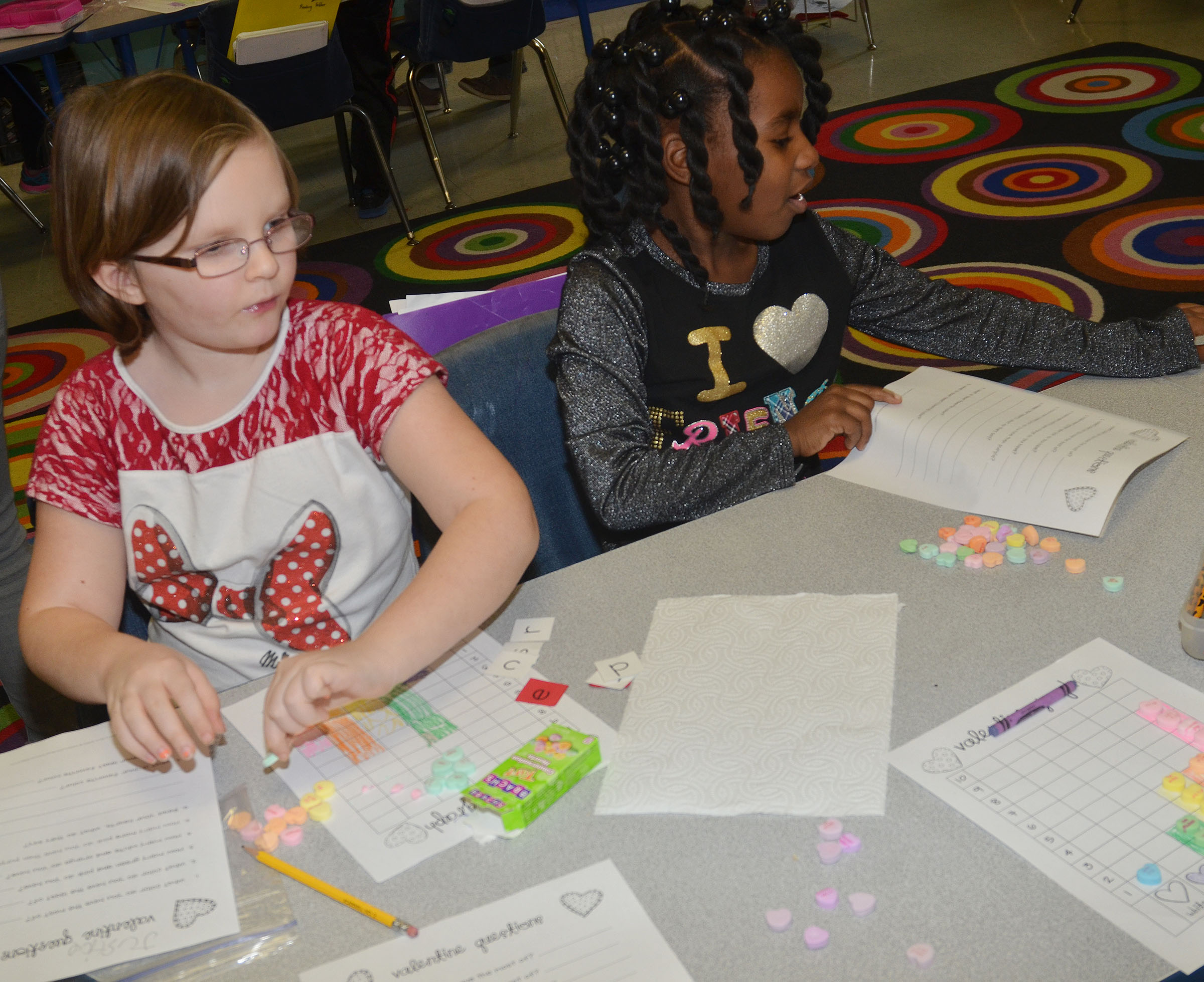 CES first-graders Justice Albrecht, at left, and Destini Gholston work on their graphs.