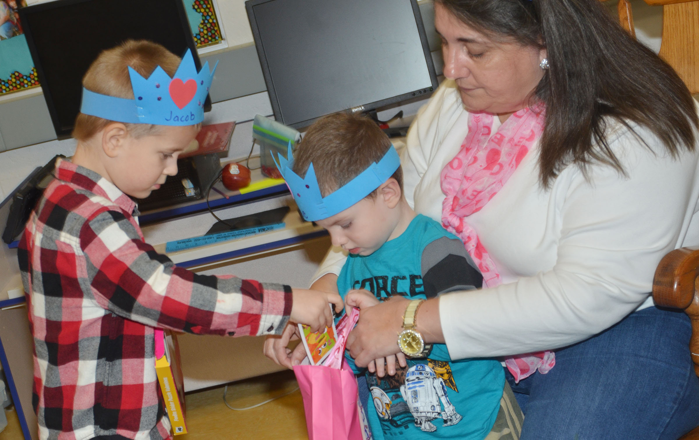 CES preschool student Jacob Parrish gives classmate Chase Arnett a valentine, with some help from teacher Sherry Cowherd.