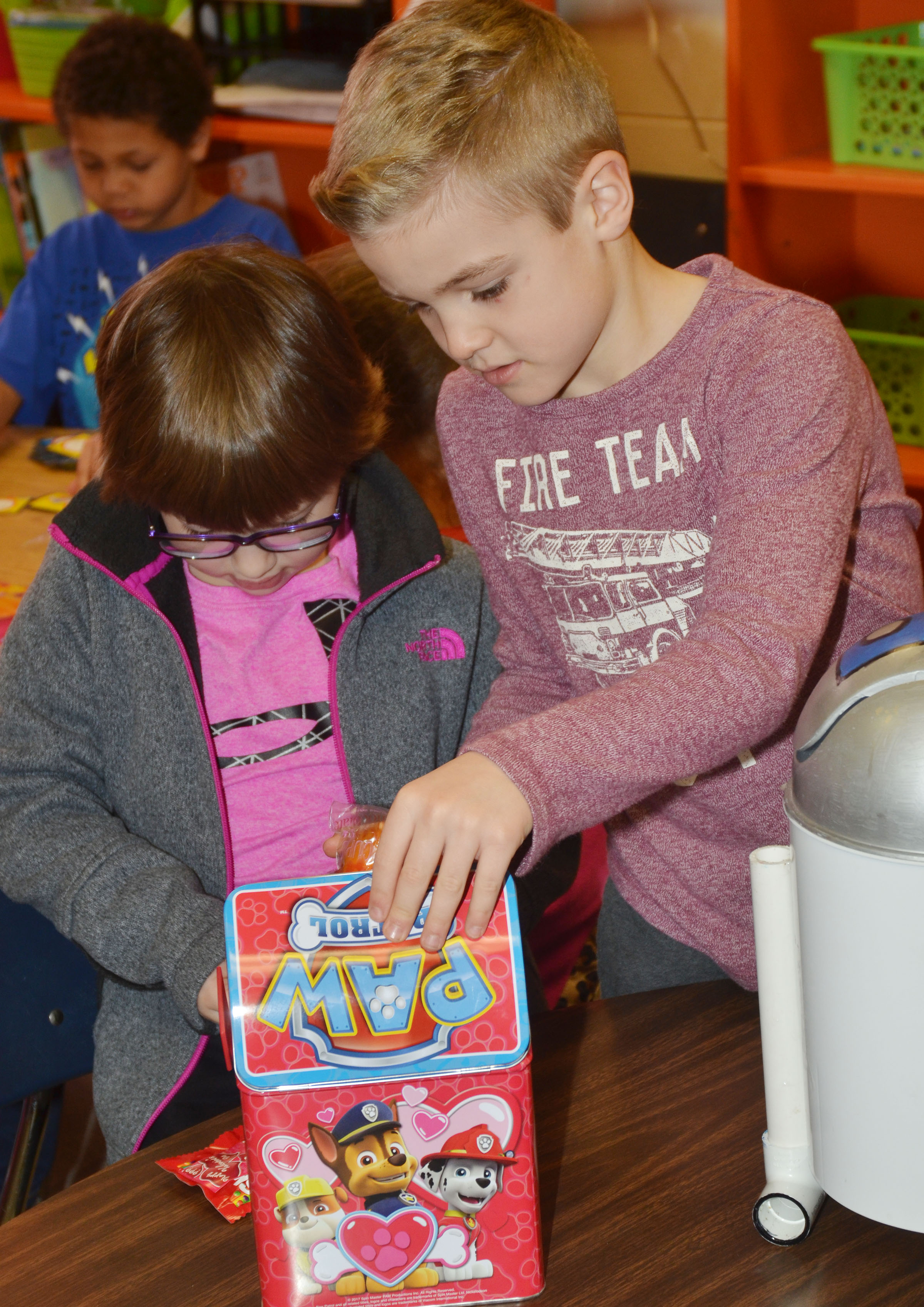 CES first-graders Addelyn Dooley, at left, and Dax Gray pass out valentines.