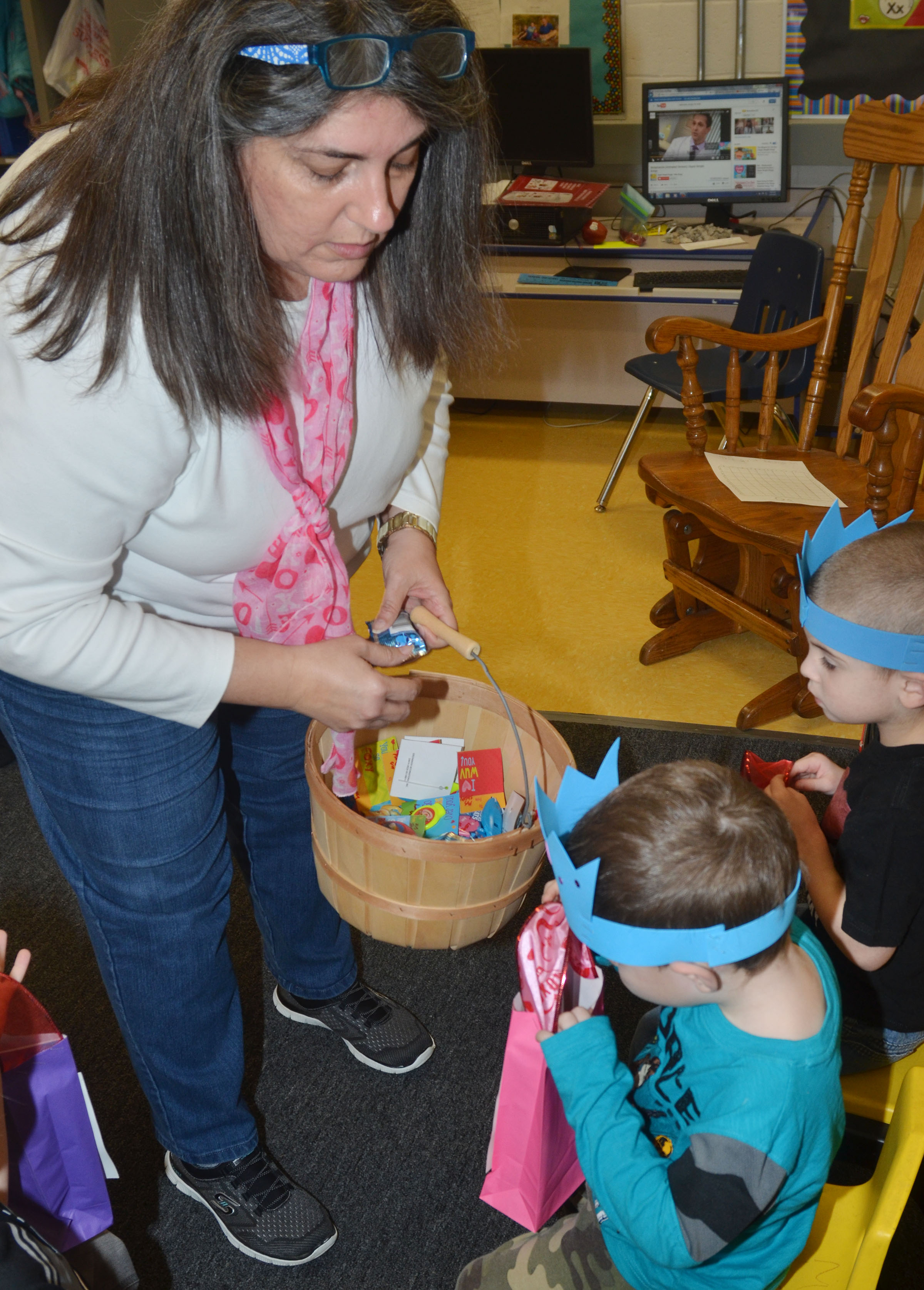 CES preschool teacher Sherry Cowherd passes out valentine gifts to her students.